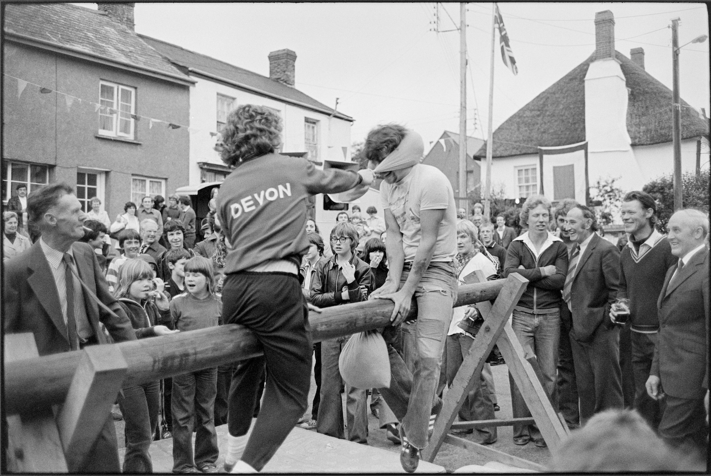 Village fair, pillow fight on greasy pole, Winkleigh, August 1980. Documentary photograph by James Ravilious for the Beaford Archive © Beaford Arts