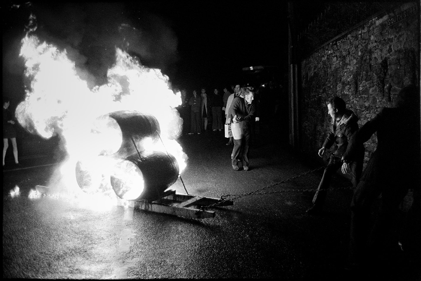 Burning tar barrels pulled through the street at night, Hatherleigh, 6 November 1974. Documentary photograph by James Ravilious for the Beaford Archive © Beaford Arts