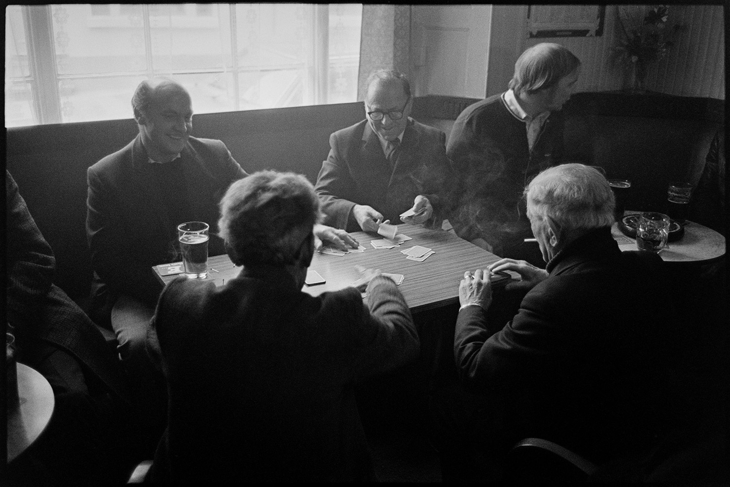 Men drinking and playing cards in pub, Torrington, December 1977. A documentary photograph by James Ravilious for the Beaford Archive.
