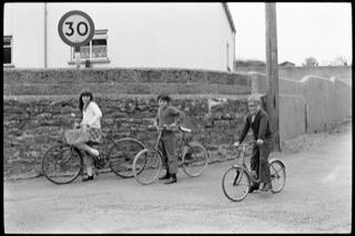 Four children on bicycles, Winkleigh, April 1974. Documentary photograph by James Ravilious for the Beaford Archive © Beaford Arts