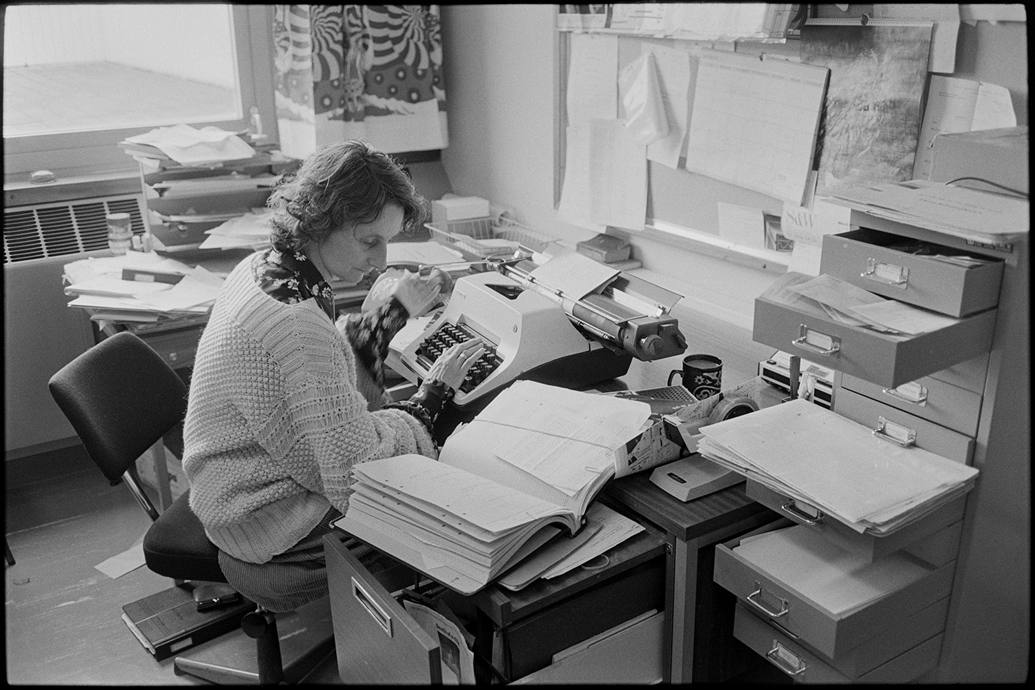 Hospital Doctor's Secretary at her desk tying, Barnstaple General Hospital, March 1984. Documentary photograph by James Ravilious for the Beaford Archive