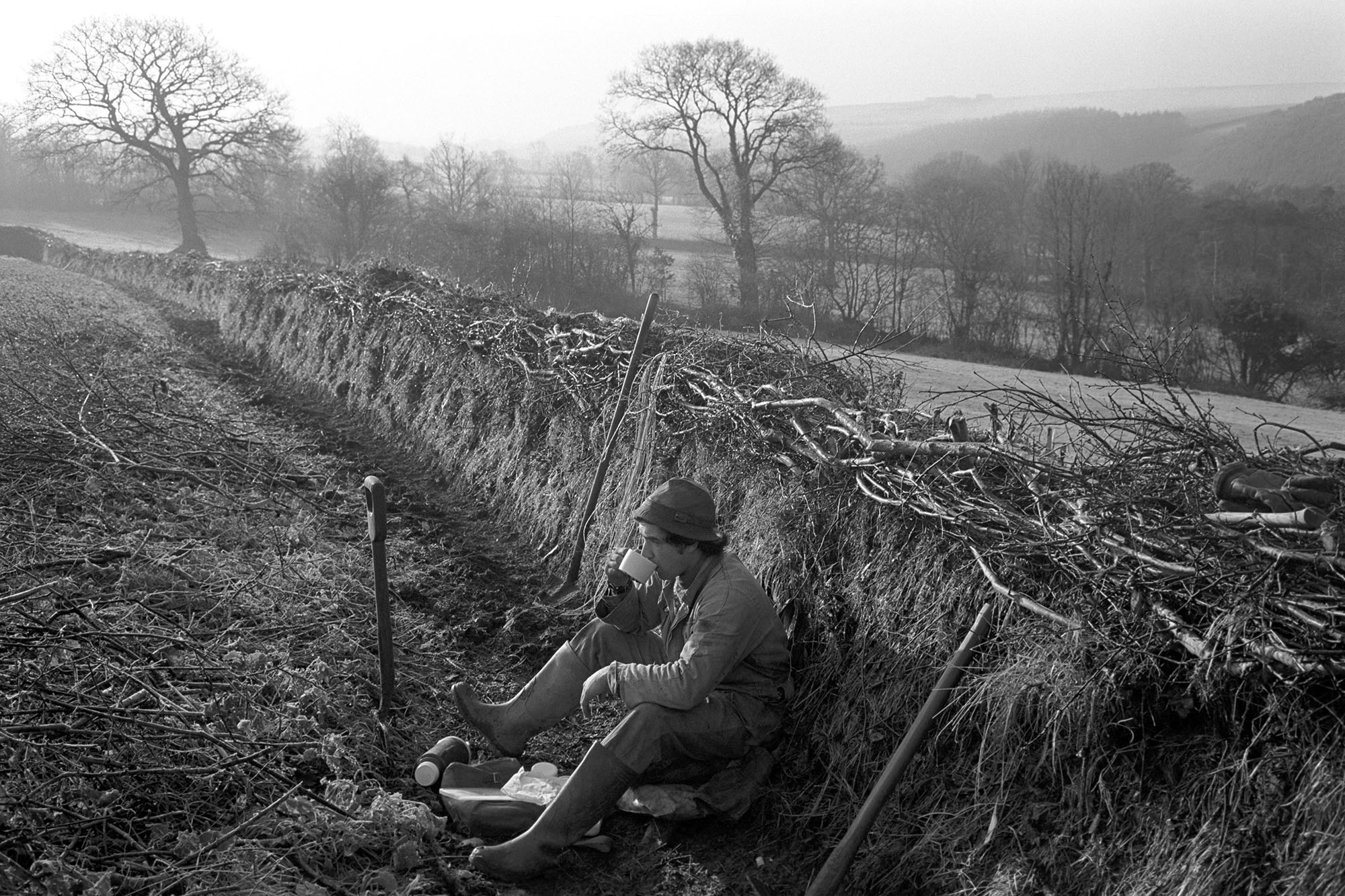 'Hedger's Lunch Break' taken in Langham, Dolton, 1980 by James Ravilious for the Beaford Archive
