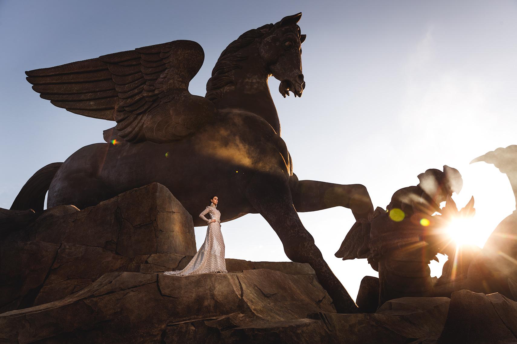 Model posing below Pegasus statue at the Pegasus World Cup Invitational