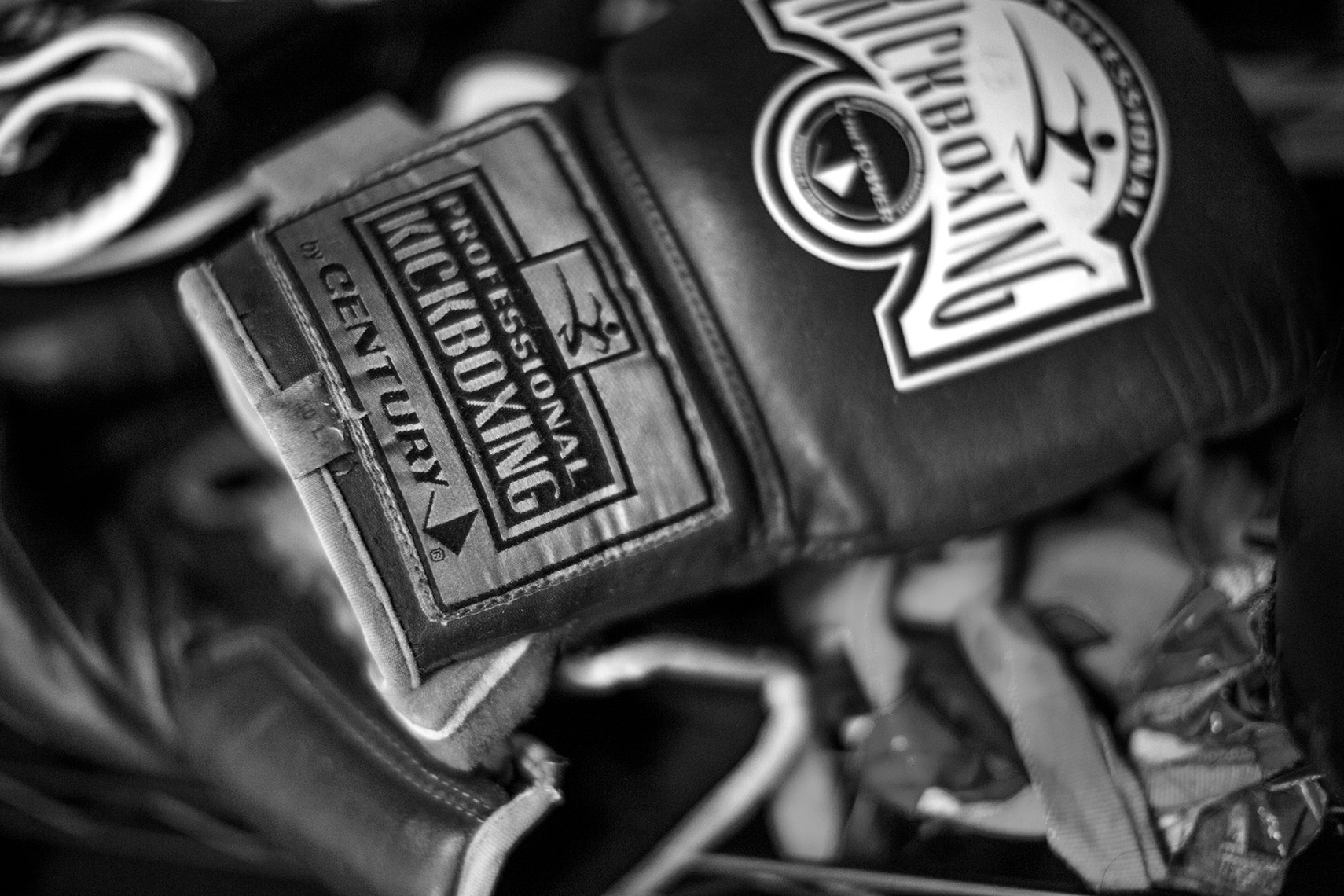 Black and white picture of their regulation kickboxing training gloves lying on the mat