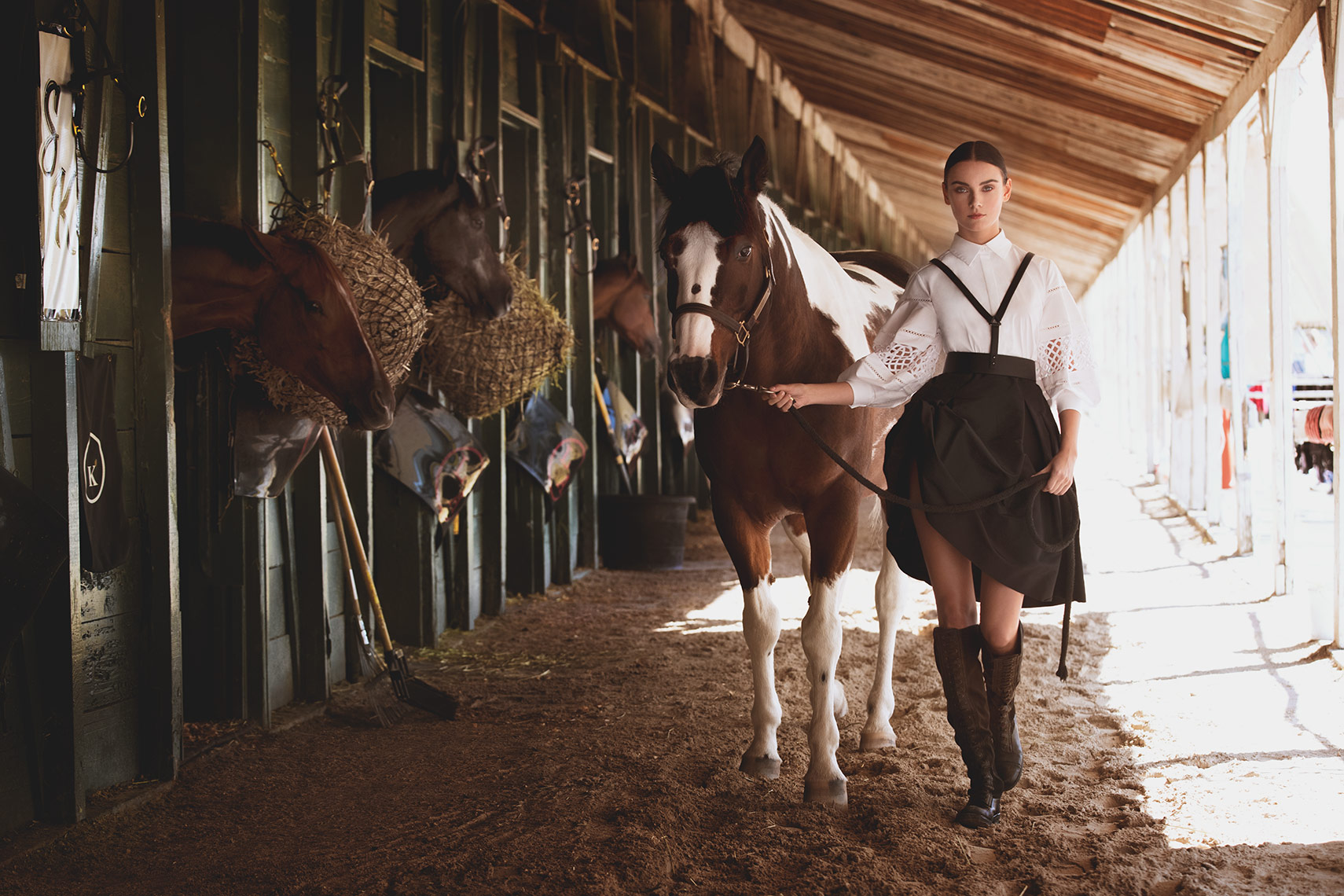 Model walking through stables with Thoroughbred Horse