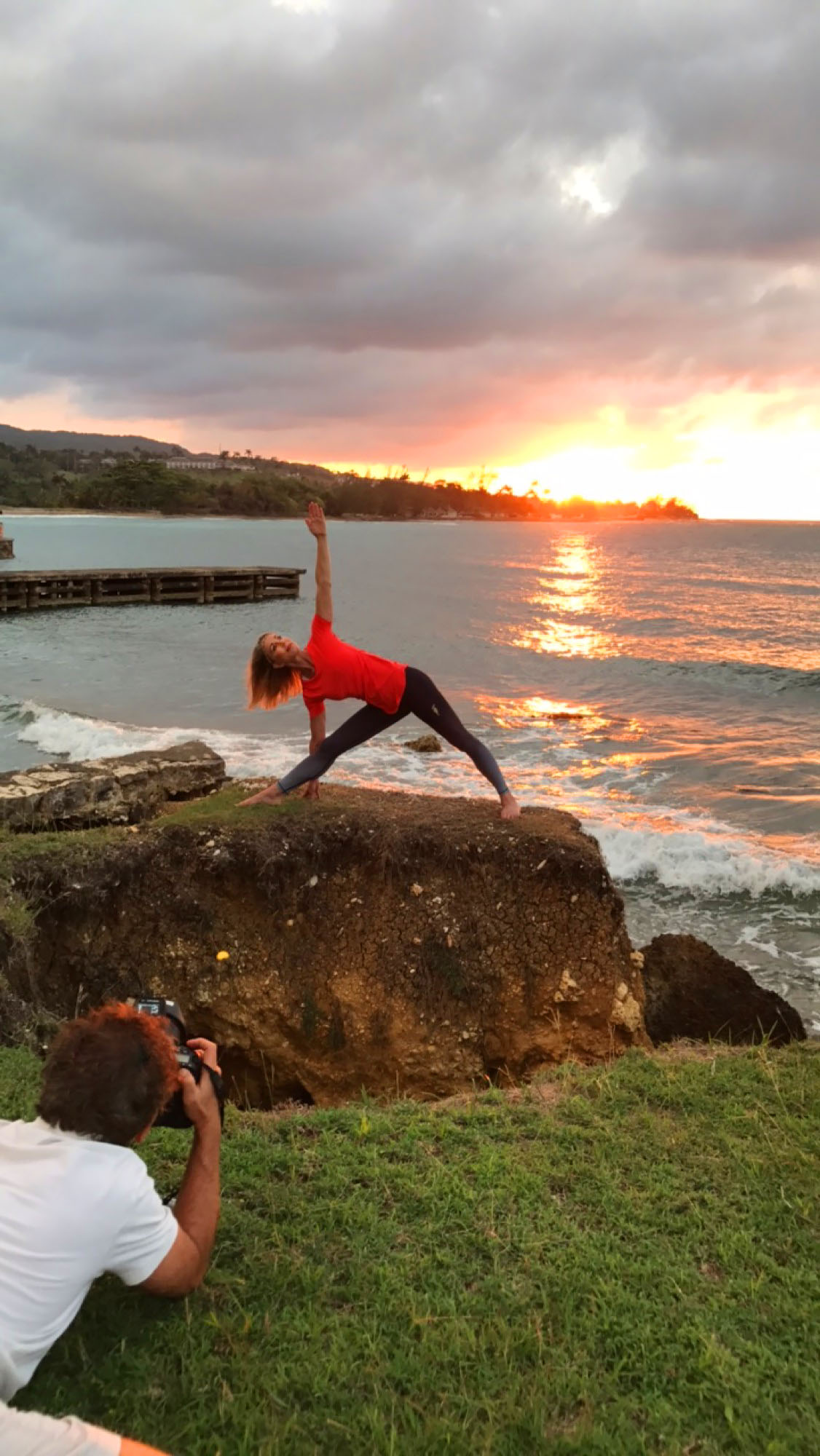 Stency Wegman performing Trikonoasana by the ocean during sunset