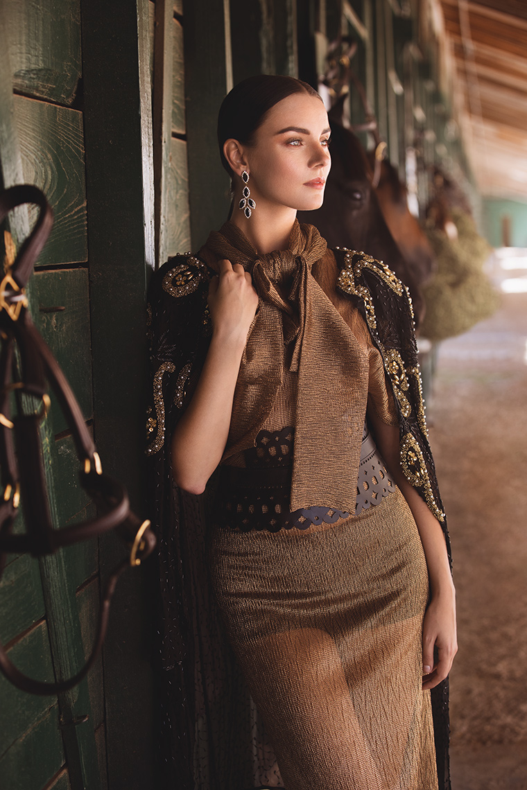 Model posing next to stable door with Horse behind her
