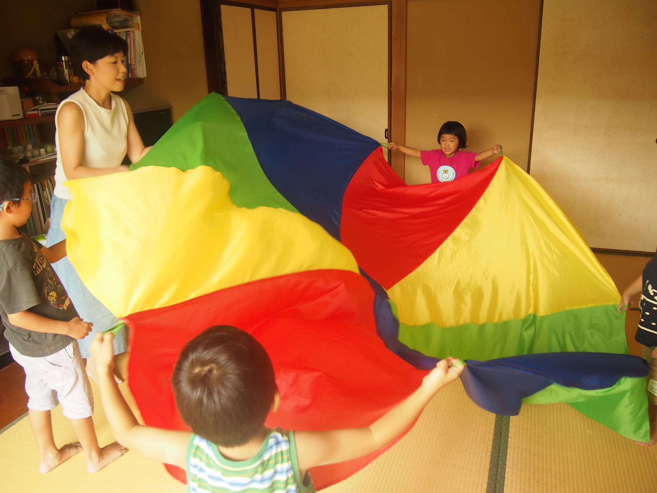 """""""My Balloon(わたしの風船)""""というソングに合わせてパラバルーンを上げたり、下げたりしながら楽しんでいます。同時に、色の名前を憶えていきます。"""