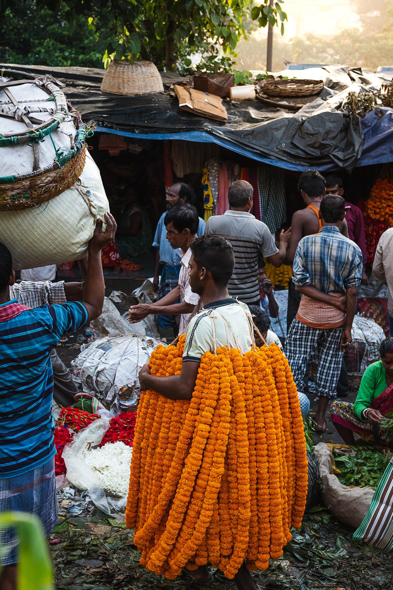 Mallik Ghat Flower Market - vendor carrying marigold chains