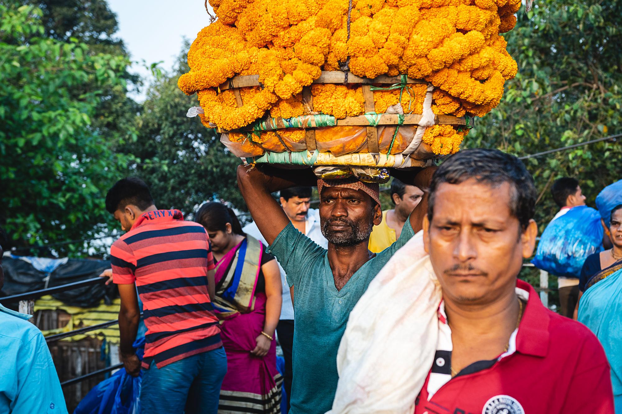 Mallik Ghat Flower Market - labourer carrying flowers on head