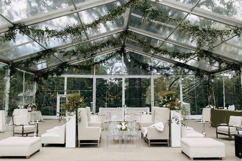 banquettes, club chairs, ivory ottomans, clear tent