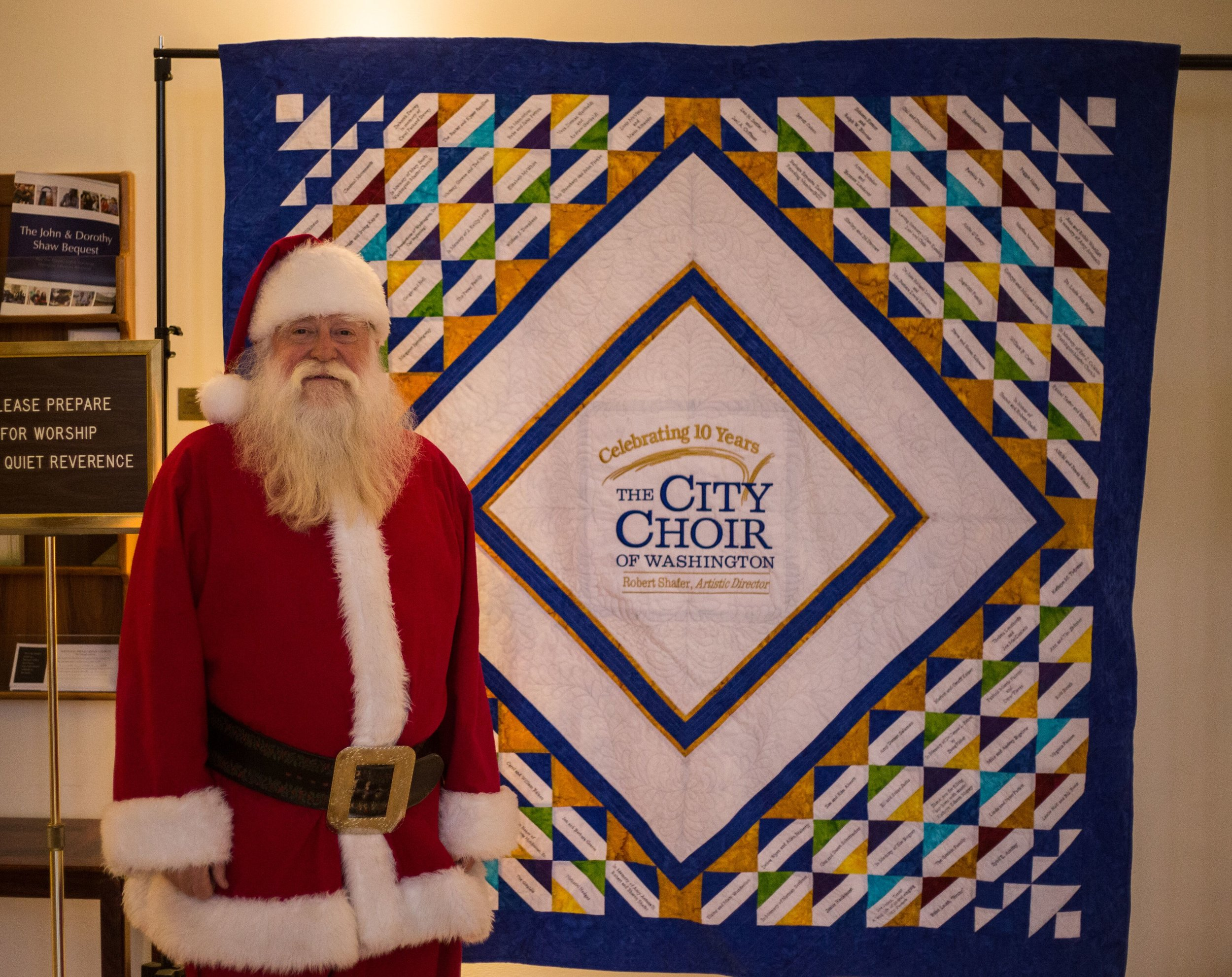 "December 2018, ""Santa"" Steve Schuers with the City Choir 10th Anniversary quilt"