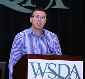Dr. Oleg behind podium speaking