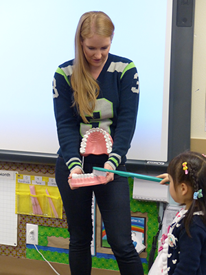 Dr. Nikole in a school showing child how to brush giant teeth