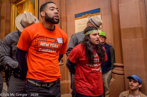 Patrick Houston from New York Communities for Change and Santosh Nandabalan from Food & Water Watch are led out of the Capitol in handcuffs.
