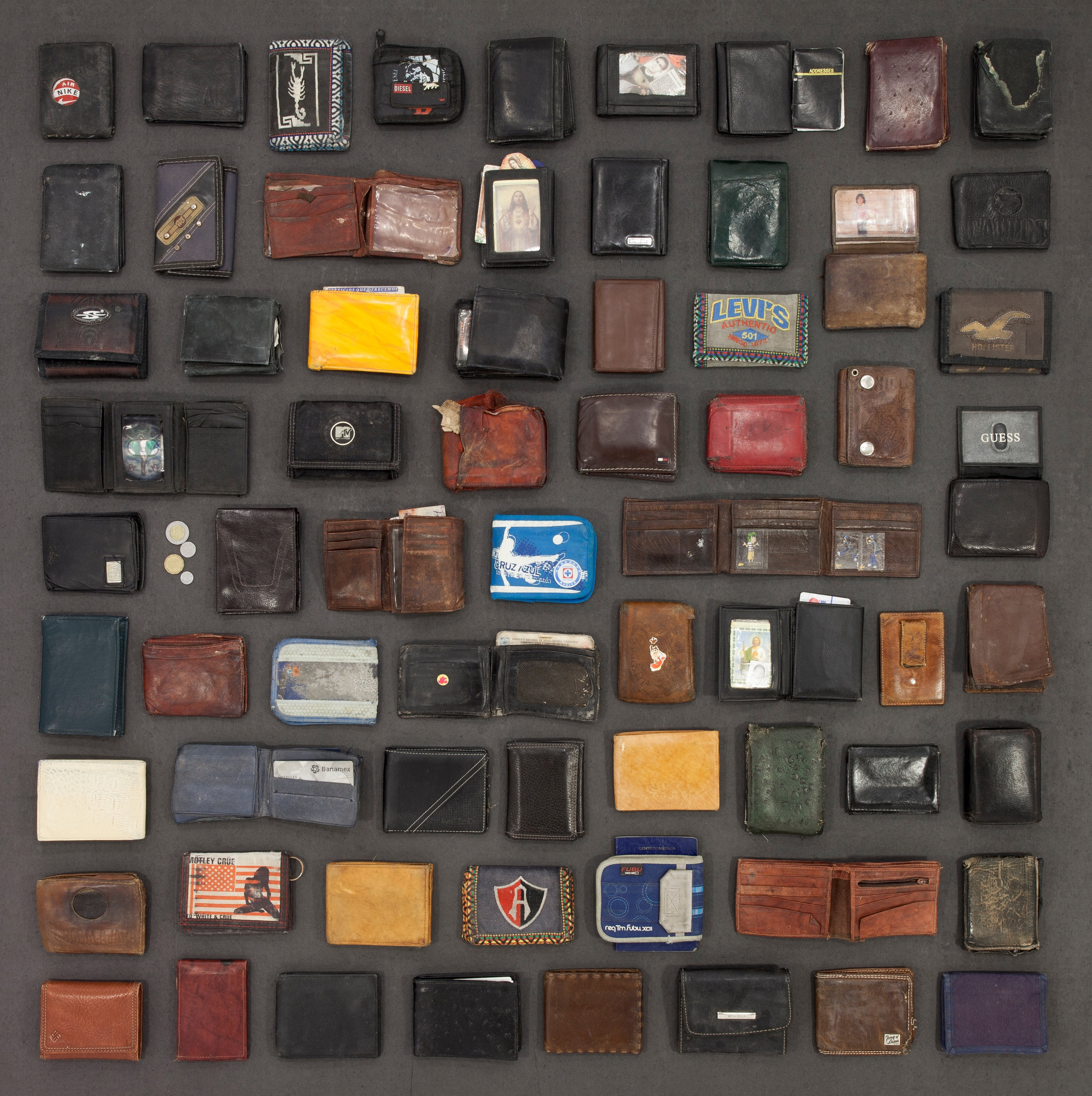 """After being apprehended, the belongings of a migrant are supposed to be placed in a property bag or remain in the backpack they traveled with. Sometimes, wallets are discarded or mistakenly left behind when they are transported to various law enforcement facilities. They are deported with no identification.  Billfolds and Wallets  Medium: Photography  Dimensions: 36 x 35.25 x 1.5  Year of Creation: 2013  Price $3,800 (framed); $3,200 (unframed 36"""" x 36"""" print)  For sales inquiries, please contact dlutzick@yahoo.com with Winslow Arts Trust Museum"""