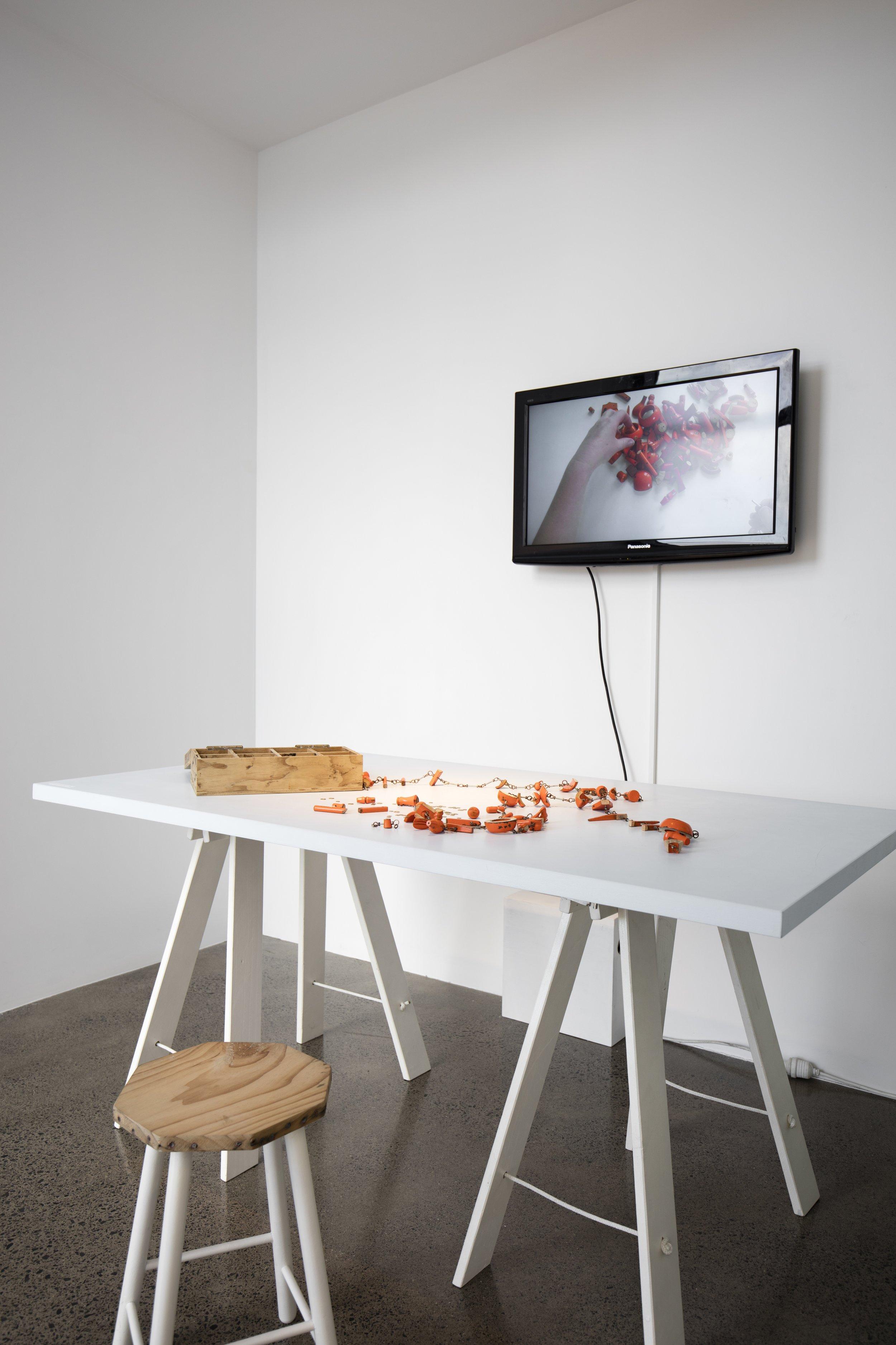 Sarah Walker Holt,  Kitset , 2014. Wood, acrylic paint, copper, brass, nuts and bolts, plywood box, digital video (5.39 mins), trestle table, stool. Courtesy of the artist and Te Uru Waitākere Contemporary Gallery. Photo: Sam Hartnett.