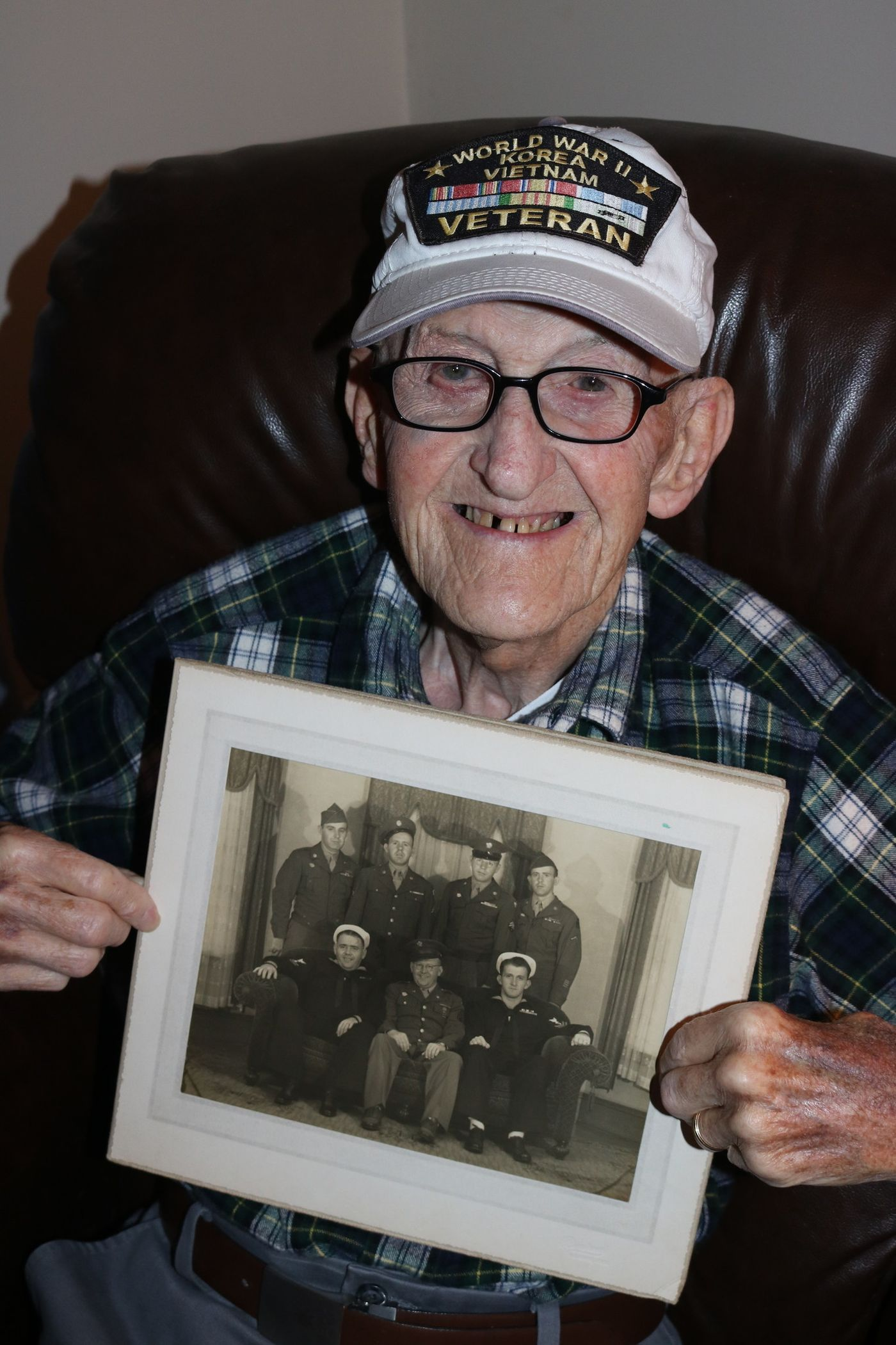 My dad, Andre Lussier, holds a photo of his brothers while wearing his hat
