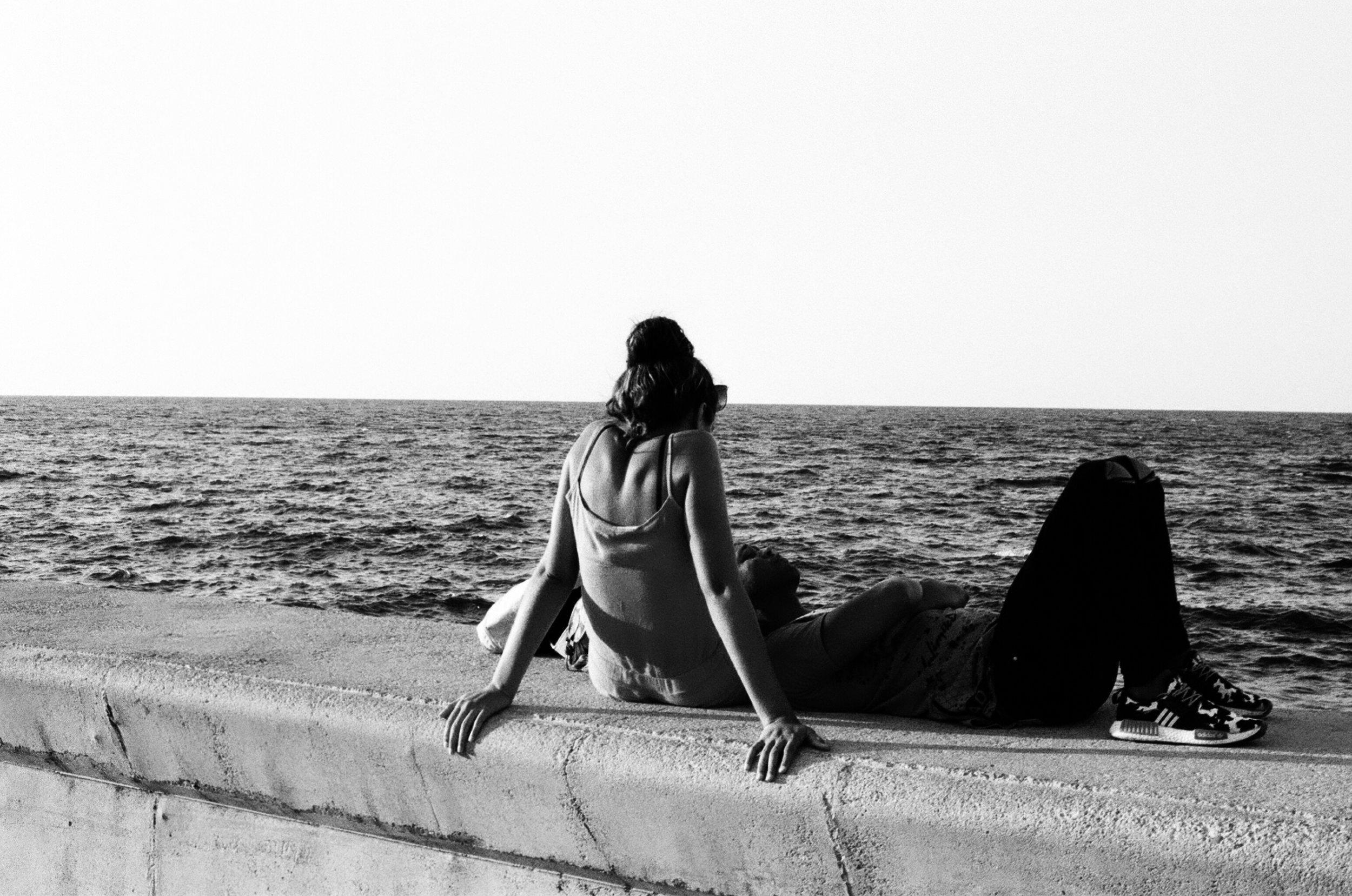 Jeune couple profitant du bord de mer, le célèbre Malecón, pour se reposer et penser à l'avenir.