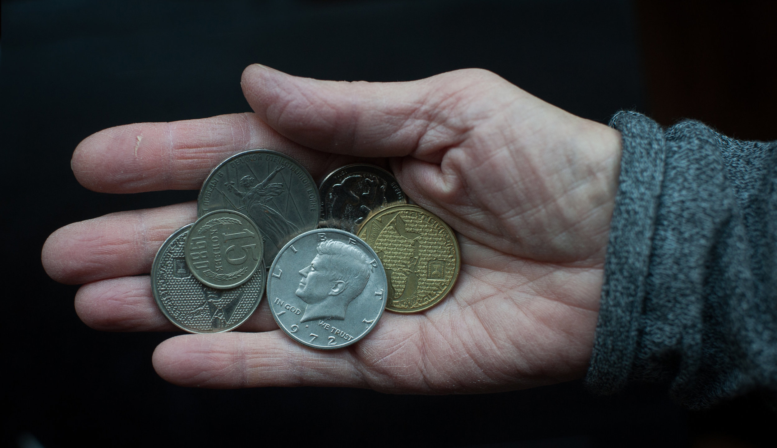 Phil's mother, Elena, holds coins worth well more than their face value to her, as they carry bits of her history. She came to the U.S. from Ukraine in 1981, when it was still part of the USSR. A Russian ruble dedicated to the 30th anniversary of victory in WWII reminds her that, as a baby-boomer, she's lived her life in the shadow of that war. She keeps a coin minted a year before her emigration to the U.S., a Kennedy half-dollar, and Israeli shekels left over from her trips to Israel.