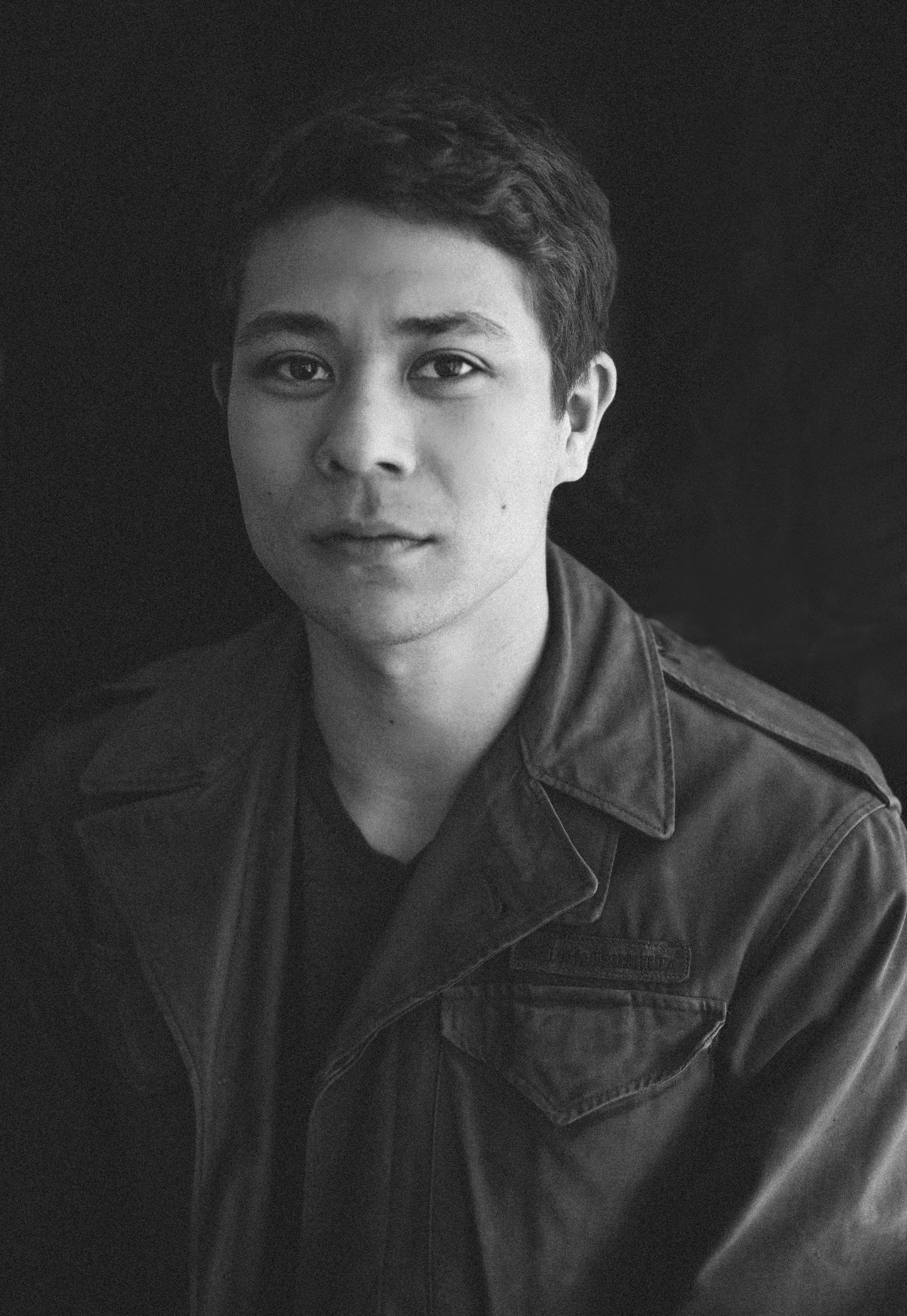 """Elaine's older son, Josh, 27, wearing his grandfather's Army jacket, tries to understand the paradox of Akira's military service: """"you're being asked to prove your loyalty to a country that denies you your civil rights and denied your family [its] civil rights."""" His grandparents' experience in the camps has shown him """"the need to be in solidarity with minorities and to stand up against injustice."""" Josh now works in Chicago with RefugeeOne, helping refugees get jobs and become self-sufficient."""