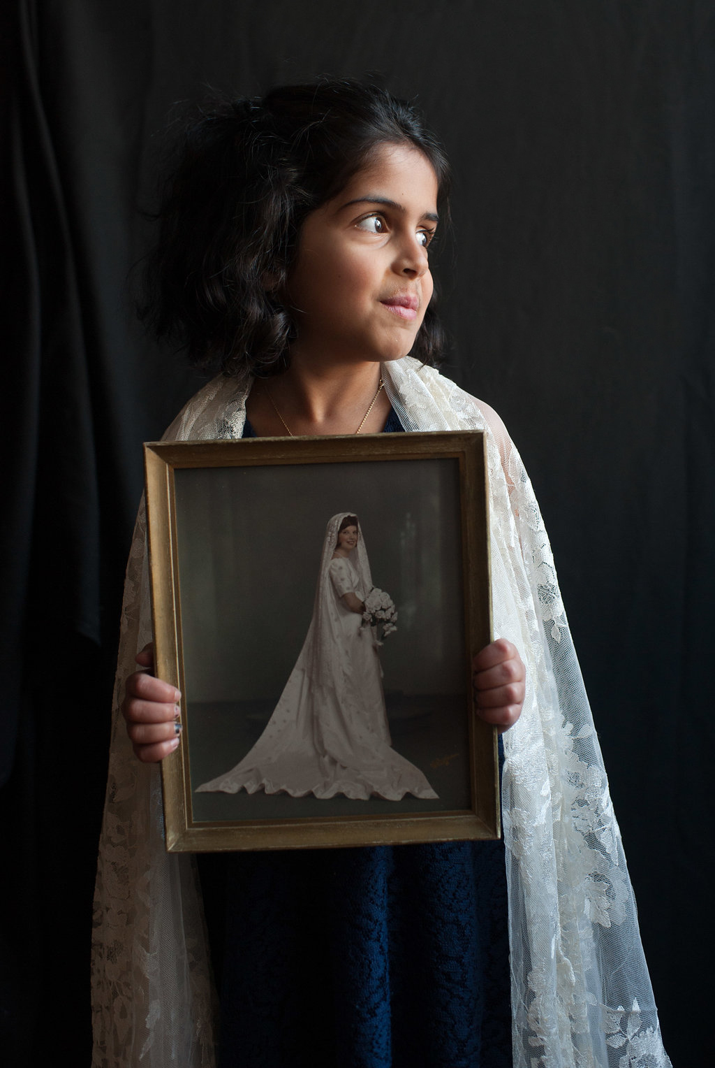 """The woven threads of a family come together in one veil. Anita and Chaitanya's young daughter, Amelia, holds a photo of her grandmother Charlotte at age 20 on her wedding day. Both are draped in the same mantilla. Charlotte says, """"The mantilla actually is a gift from my husband's family. When we were married his sisters made the mantilla to wear on our wedding day. And Anita also wore it when she was married to Chaitanya."""""""