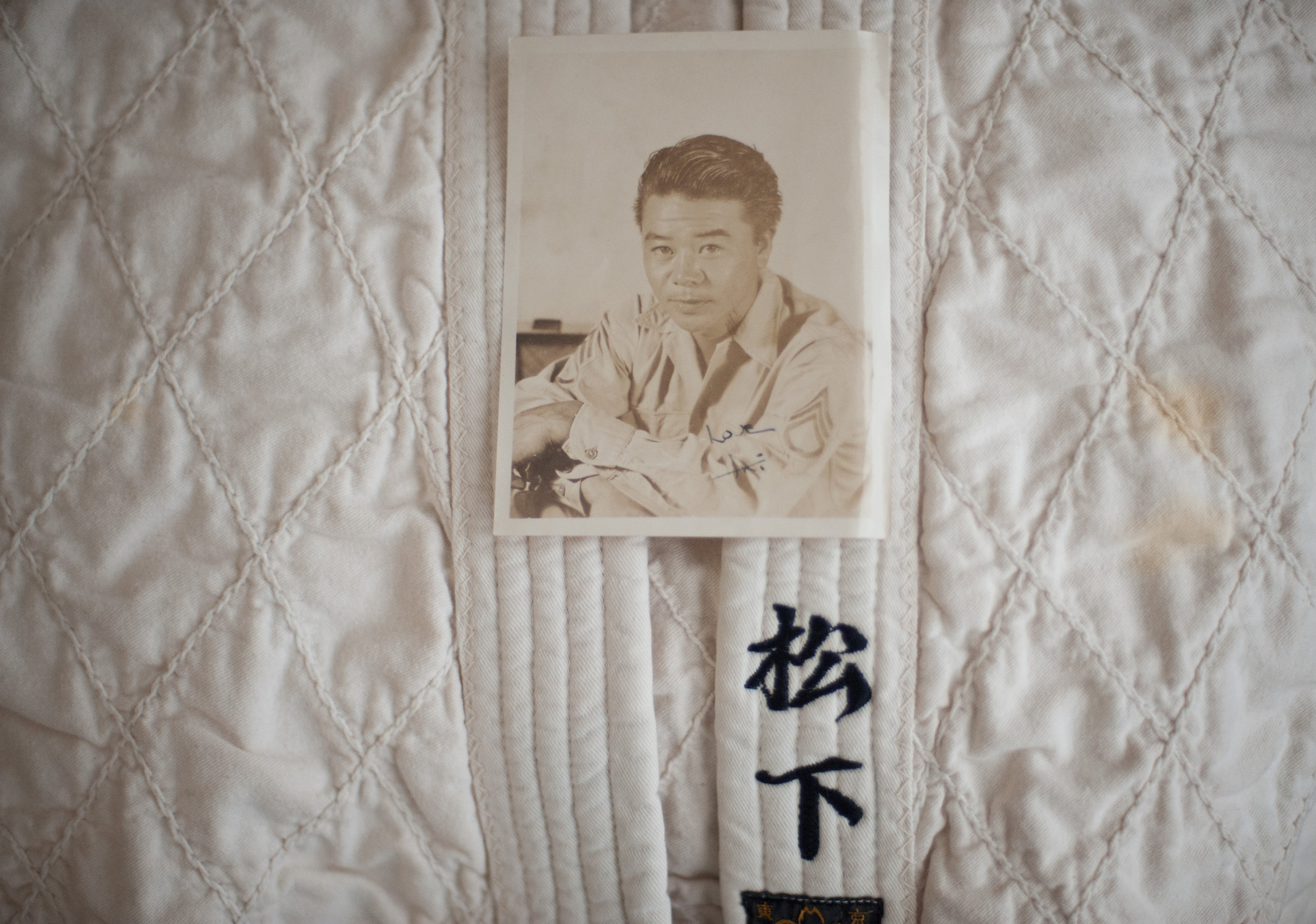 """Akira Matsushita, seen here in an official Army portrait signed """"Love, Aki,"""" earned a black belt in judo before the war. Elaine treasures his old judo robe, or  gi , embroidered with his name in kanji characters. When Elaine's brother was young, Akira drove him to judo; he also got a black belt. Later, when his grandsons were kids, he drove them to judo, too."""
