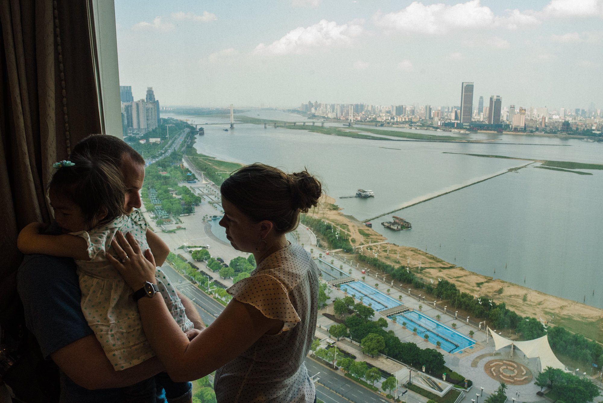 The agency official gone, Cory and Signe bring Victoria to a window looking across the Ganjiang River toward old Nanchang, calming her by showing her things within their view.