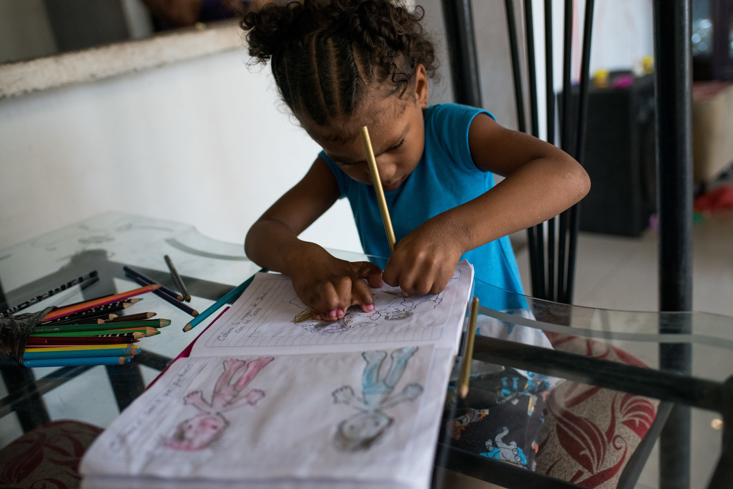 Ebony does home work. Because of her successful surgeries, she is able to hold a pencil now, and can learn to write.