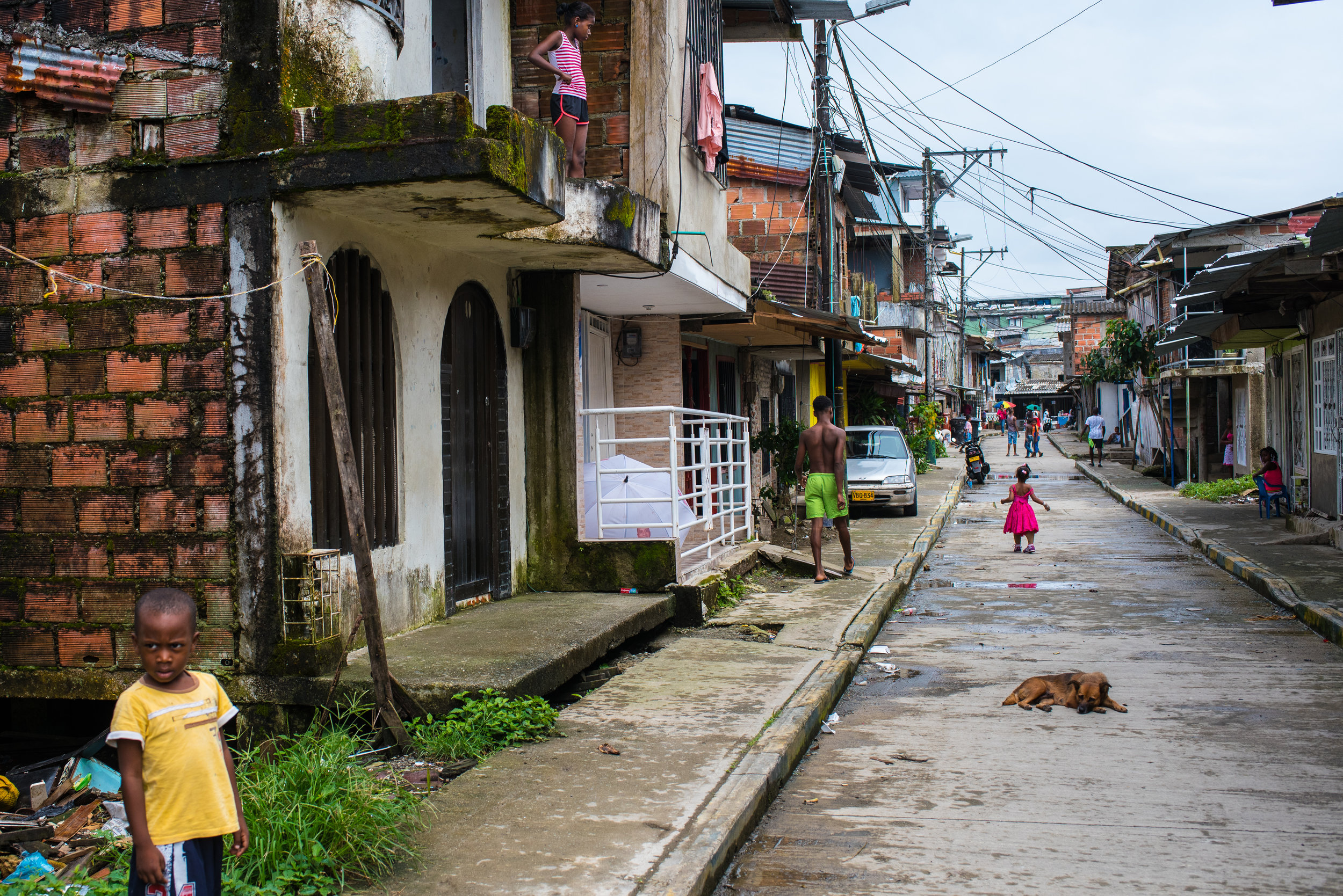 Ebony, in pink, walks on prosthetic legs down the street where she lives.