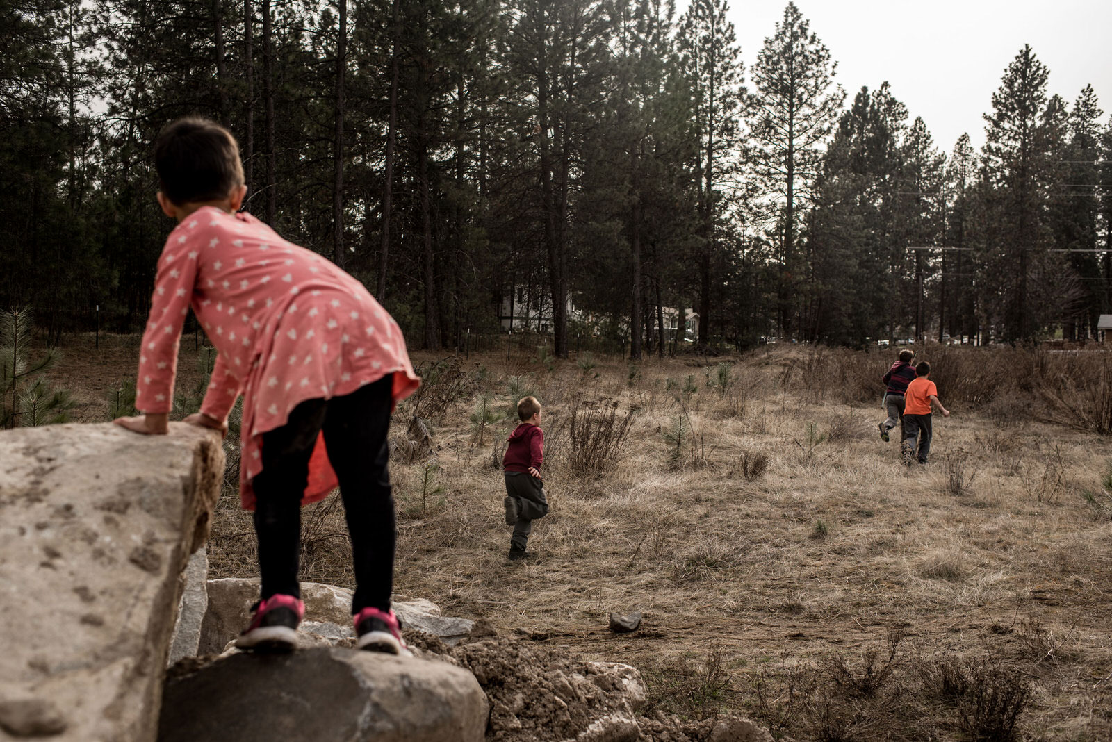 Age 5. Walking in a wooded area near our house, we saw a group of boys playing with bows and arrows. He watches curiously. At one point, he calls out to them but they don't hear or acknowledge him. As we get closer, they run off.