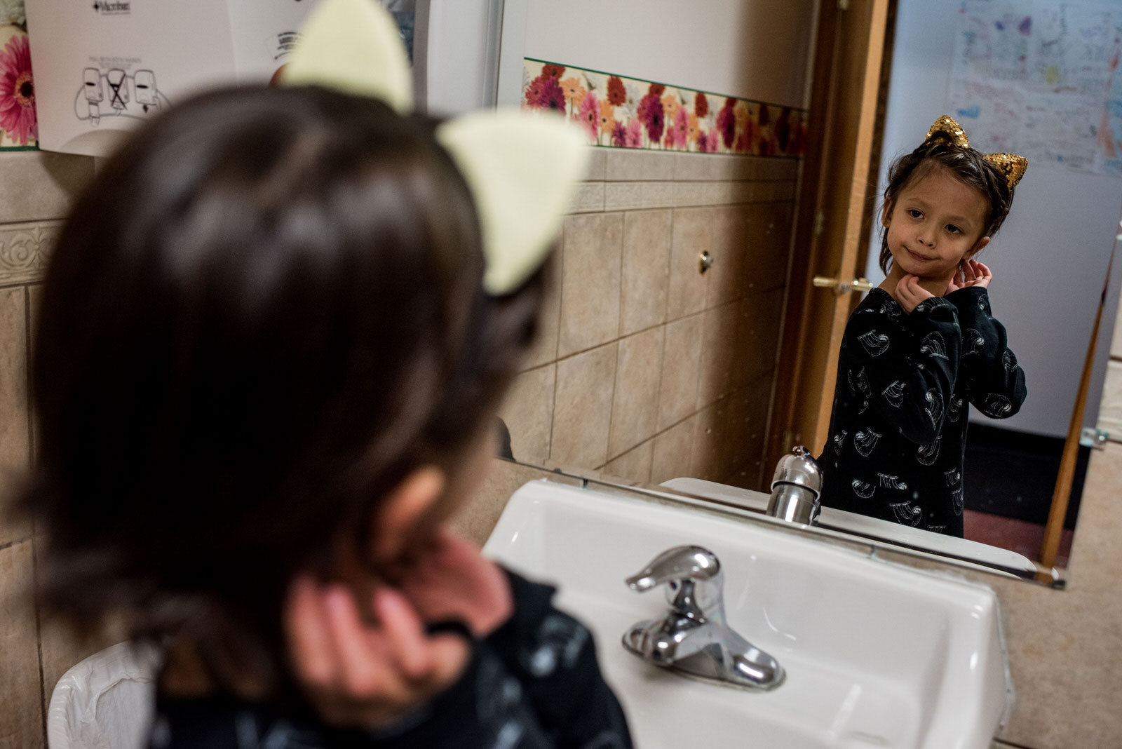 Age 6. He goes to the bathroom at a birthday party and uses the girls' restroom. The cat ears headband is a party favor. He checks his ears in the mirror before returning to the party.