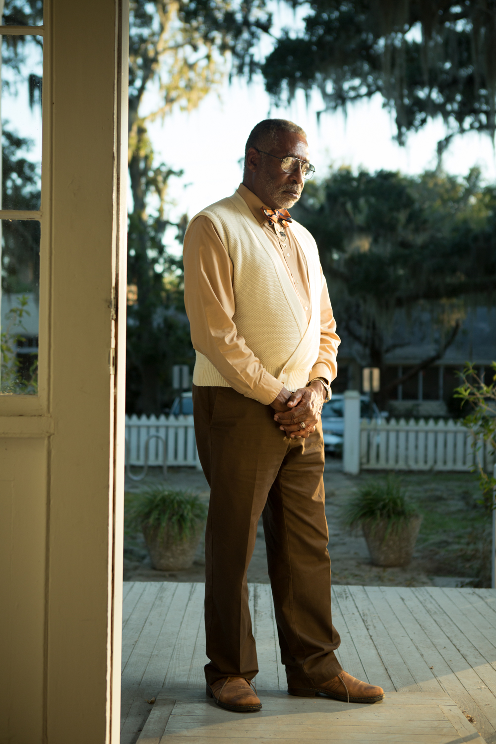 Dr. William Collins stands on the porch of a community house in Darien, heart of Georgia's Gullah Geechee culture, after a meeting. In the late 1990s, Dr. Collins, a preservationist and personal historian, discovered and purchased a plot of land that had belonged to his great-grandfather, Cain Hammond, a former slave in McIntosh County, who bought it back in 1875. Dr. Collins now lives on the land and calls it Hammond's Cove.