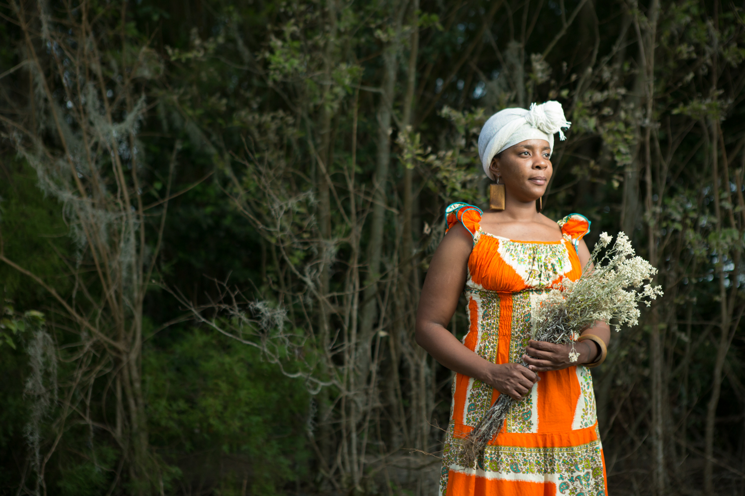 "Gullah Geechee historian Tiffany Young holds a sweet grass called life everlasting that elders use as a tea to help with lung issues. Young is a descendant of Butler Island Plantation slaves and a practicing ""Geechee griot"" or storyteller of Geechee life and history. She says her grandfather's tales ""lit a fire"" of interest in her family's past—she's traced back to where her ancestors were enslaved, as well as the voyages that brought them to Georgia in 1735."
