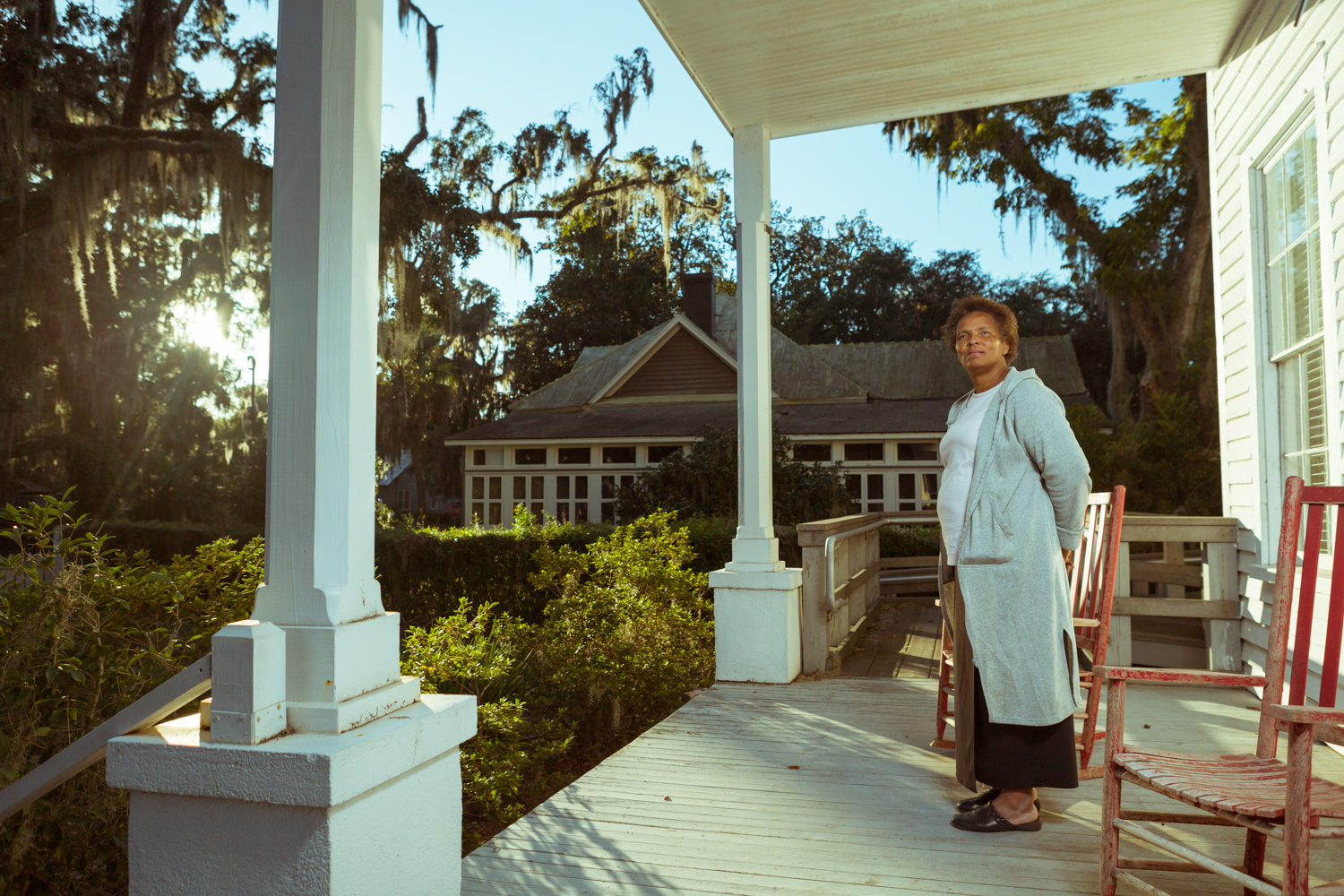 "Dolores Bailey stands on a front porch in Darien. Bailey's extended family is of Gullah Geechee descent; her mother-in-law, Cornelia Bailey, was a Gullah Geechee educator and writer on nearby Sapelo Island. One of the last generation to have been ""born, raised, and schooled"" on the island, Cornelia wrote in ""I Am Sapelo"": ""We don't want to lose the meaning of what a lot of gnats mean, how fresh-dug sweet potatoes taste cooked in hot ashes. I am Sapelo and all the hundreds of others who are descendants; we who remain here is Sapelo. We are one, bound by…high tide, fields, gossips, smoke mullet, and our faith."""