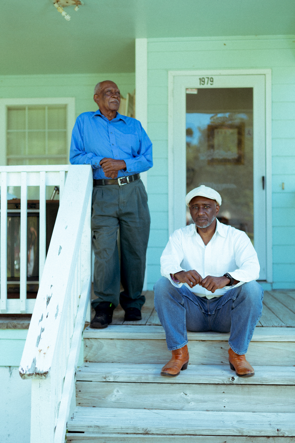 Gullah Geechee elder and county commissioner Charles Jordan stands on his front porch with his son Dwight (seated), a teacher and former member of the McIntosh County school board.
