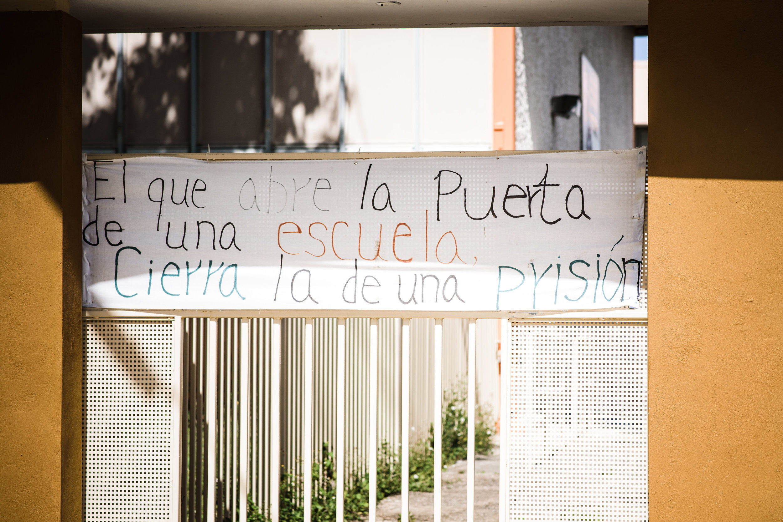 """A middle school in the Cantera neighborhood in San Juan, closed since for more than four months at the time the photo was taken.Someone posted a hand lettered sign to the locked gate: """"He who opens the door of a school closes a prison."""" The displaced students attend classes at another school nearby - a school holding more than double it's capacity of kids. The host school is an elementary school, so the older kids and younger kids had to share the younger kids' space. Photo: Aniya Emtage Legaro"""