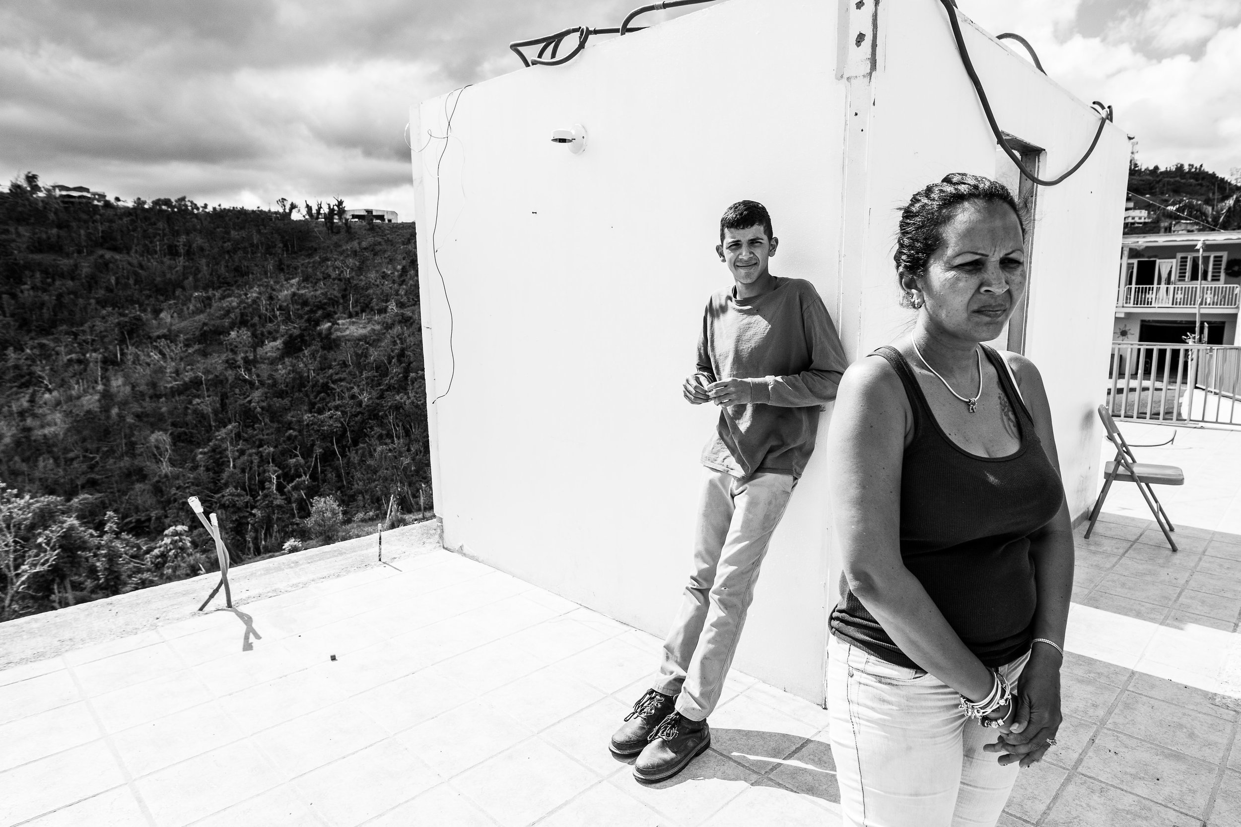 Denisse Hernández stands on the tile floor of her home, on the four month anniversary of Hurricane Maria. Her 15 year old son Javi rests against the only remaining walls of the house - the cinderblock walls enclosing the bathroom. Behind them, a breathtaking valley outside Orocovis. As her family weathered Hurricane Maria in the nearby home of her in-laws, Denisse's children watched their house lift off its foundation and plunge into the valley. Denisse ran a business from her house, so the equipment and supplies for her livelihood were lost with the house. The family is somewhat fortunate in that FEMA aid totals about $10,000. But, the estimate costs of rebuilding the home to be around $35,000. More troubling for the moment, though, is the fact that they ordered cinderblocks to begin rebuilding, and paid, in mid-November. When we visit them, the cinderblocks have yet to arrive, and they don't know when they will. It is Denise's understanding that FEMA has legal right to take any supplies that arrive in port, and she thinks maybe FEMA used their cinderblocks for something else. Meanwhile, the price of basic building supplies has more than doubled on the island. She thinks maybe US suppliers (thanks to the Jones Act, all shipments of anything to Puerto Rico have to come from US suppliers in US ships) are hiking up prices of supplies to Puerto Rico.  In mid-February, 2018, the cinderblocks arrived. They came just a few days after electricity was restored on Denisse's entire street. Photo: Katie Jett Walls