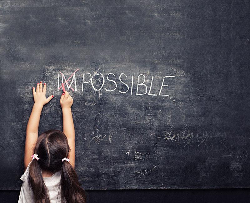 Le mot impossible est écrit à la craie sur un tableau. Une enfant rature le début du mot pour qu'il ne reste plus que le mot possible.