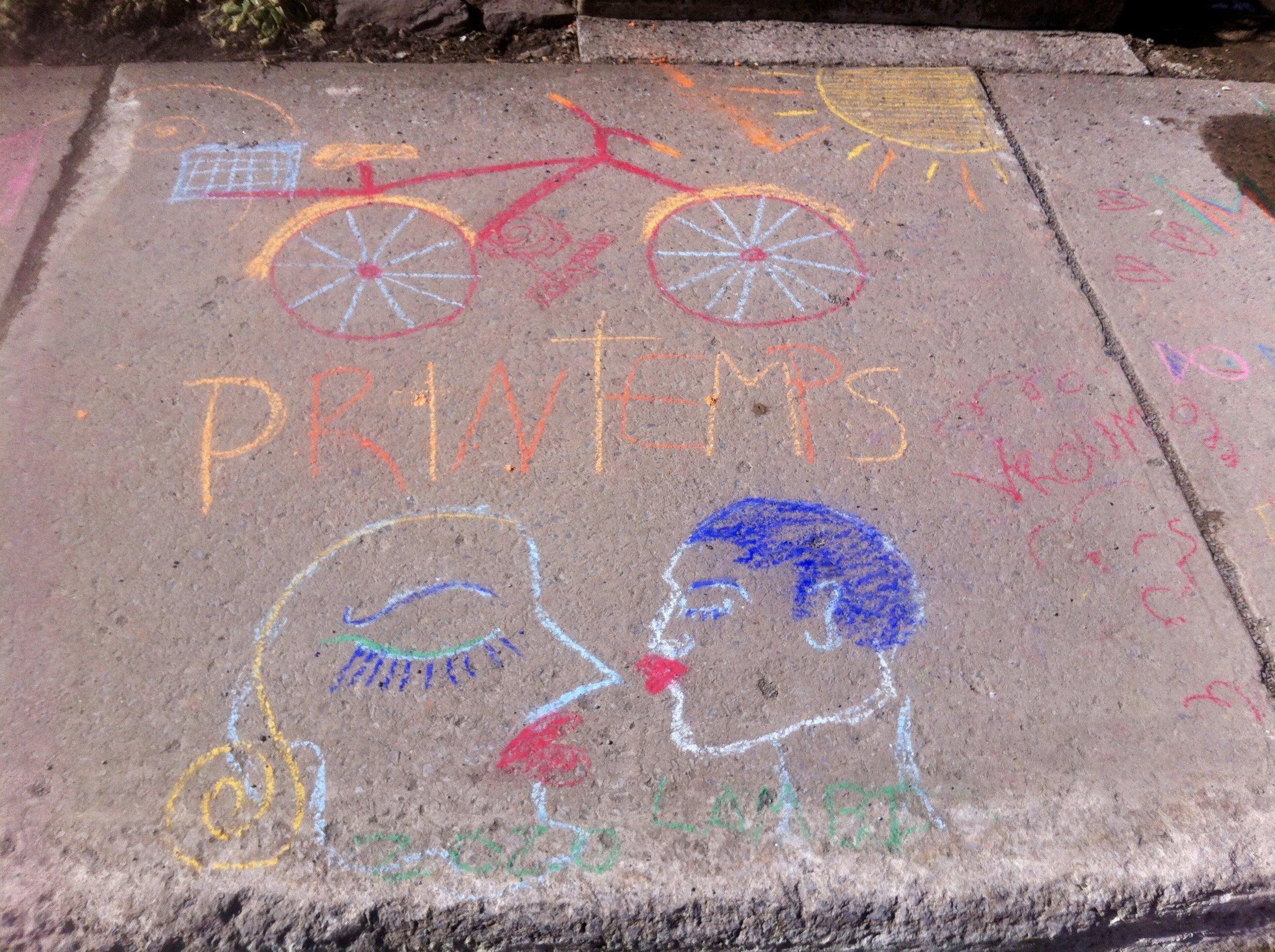 Dessin à la craie sur un trottoir ensoleillé. Printemps. Montréal. Vélo. Deux visages tracés à la craie semblent s'embrasser.