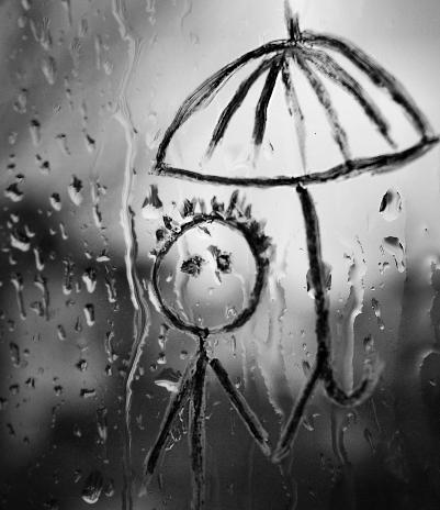 Pluie sur fenêtre. Noir et blanc. Au crayon noir et gras est dessiné un bonhomme allumette tenant un parapluie.