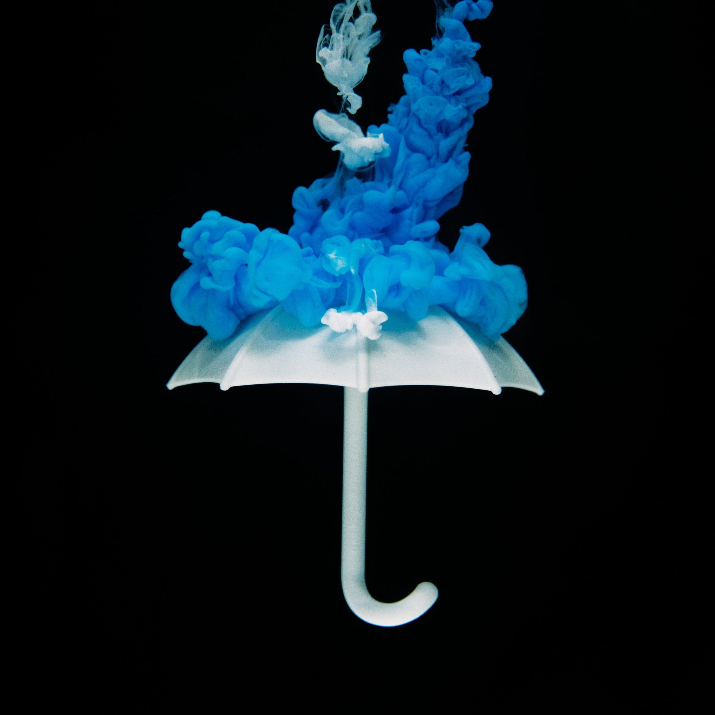 Sur fond noir, un parapluie blanc. Au-dessus de lui, un nuage de fumée bleue et blanche.