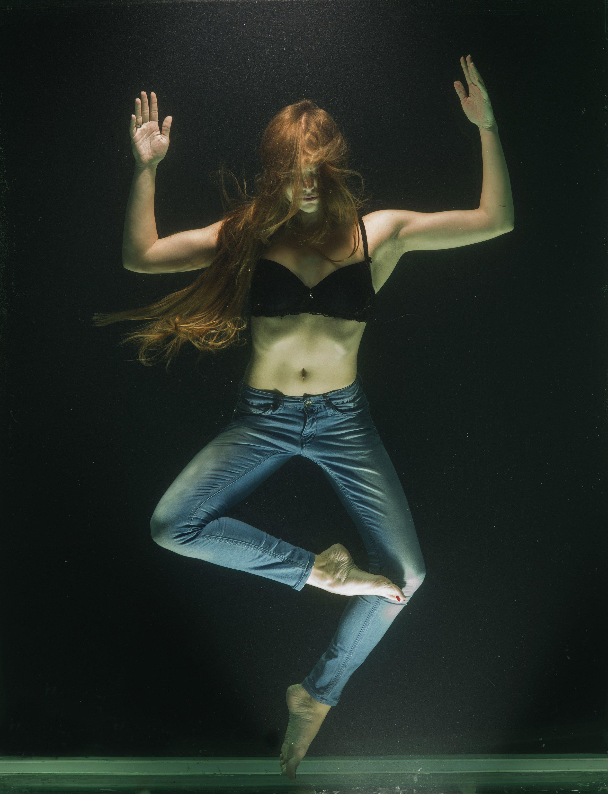 Une femme sous l'eau. Ses cheveux longs, roux et lumineux recouvrent son visage. Ses jambes sont repliées dans une posture dansée et semblent former une figure géométrique.