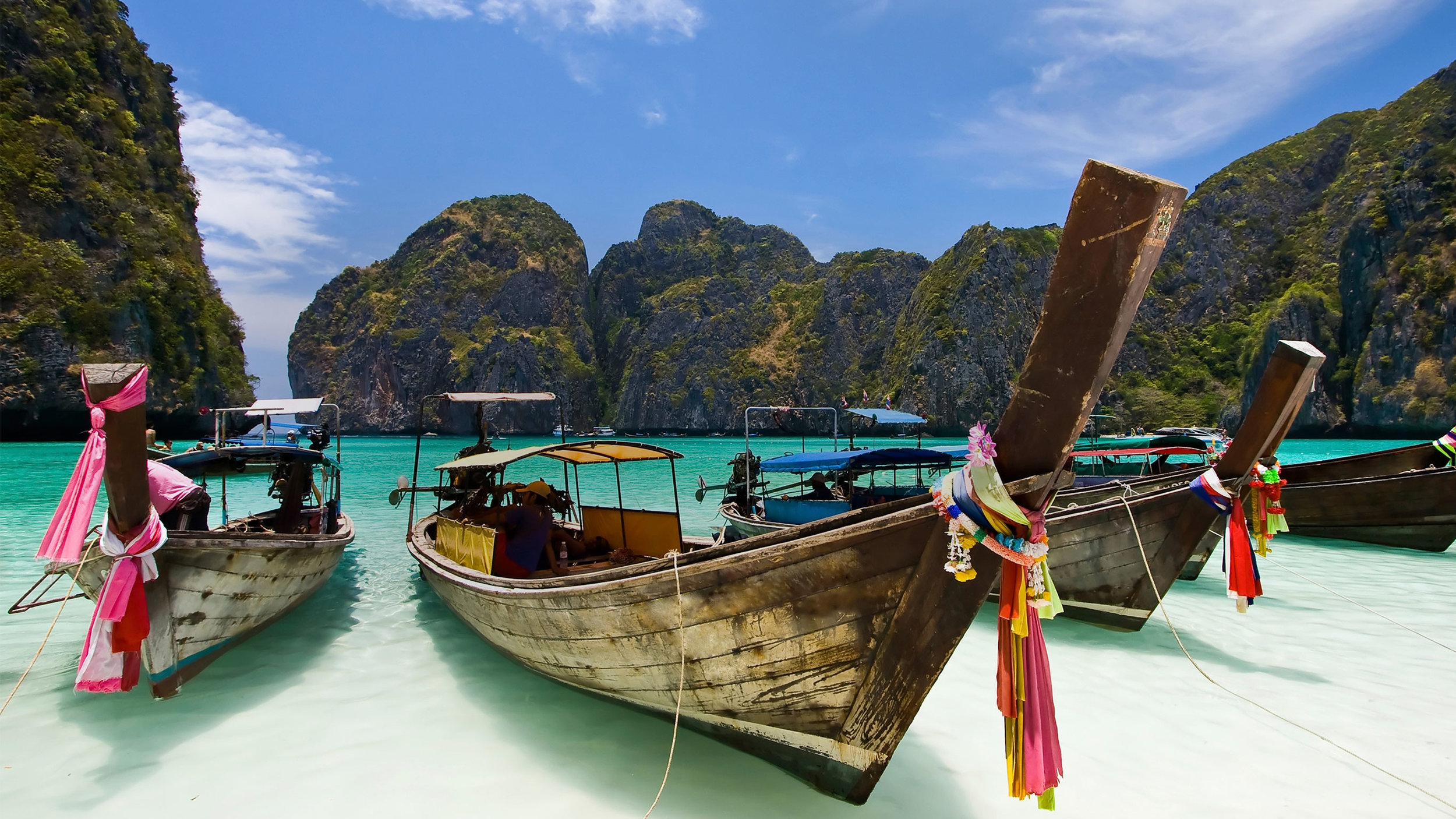 Long tail boats rest amongst limestone cliffs awaiting their next charter in Phang Nga Bay.