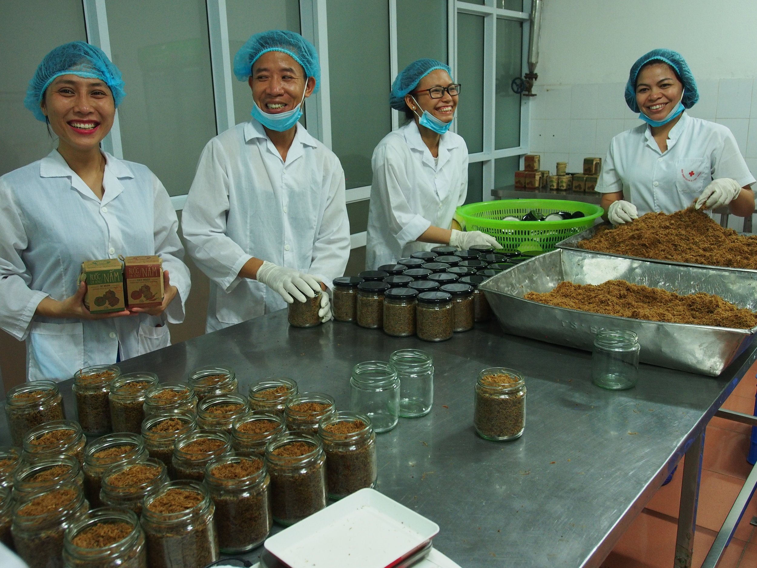 Owner Pham Hong Van with employees in Smiling Mushroom's production facility