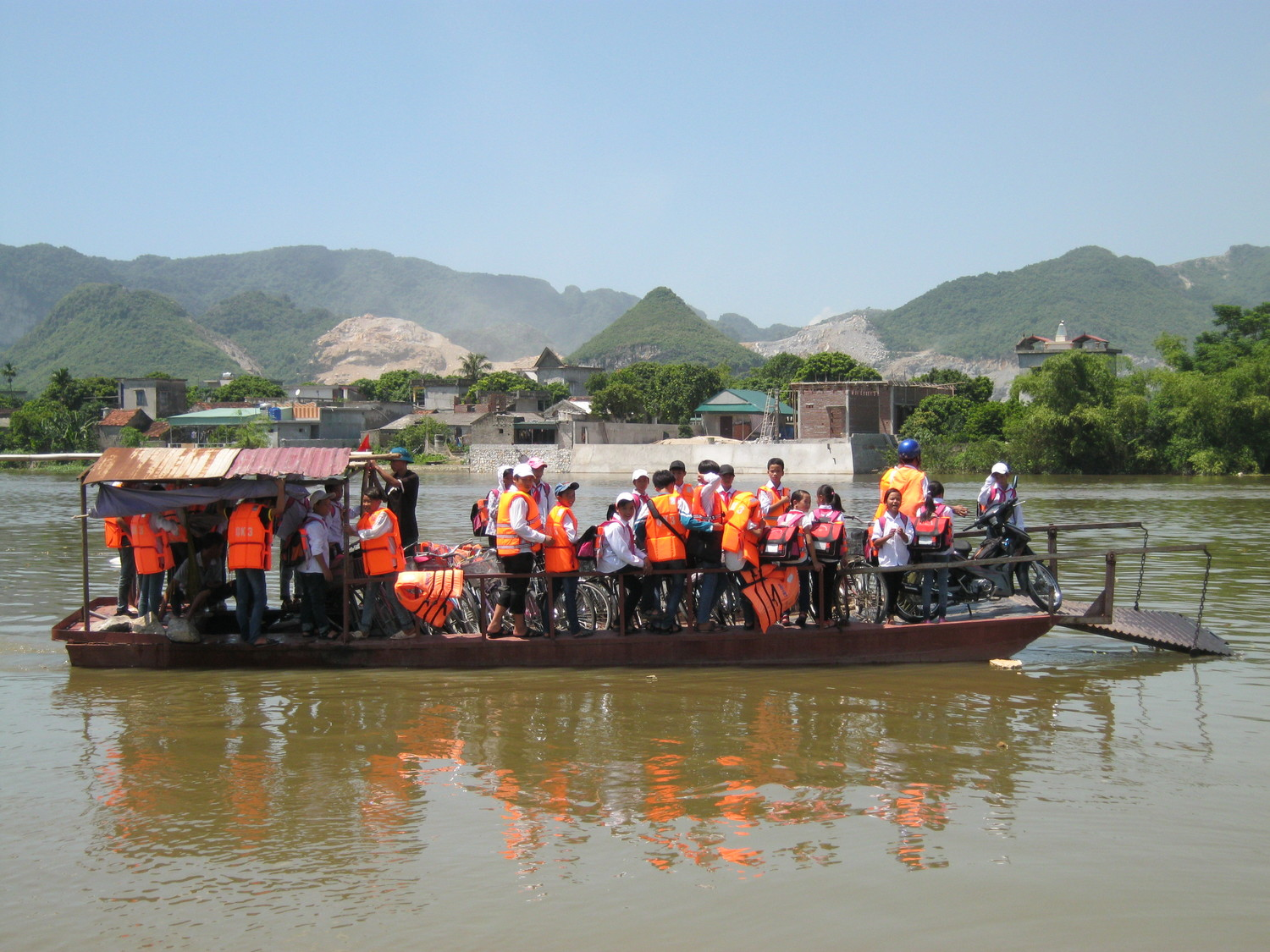 """Students crossing the river on daily commute to and from school using a """"safer"""" boat."""
