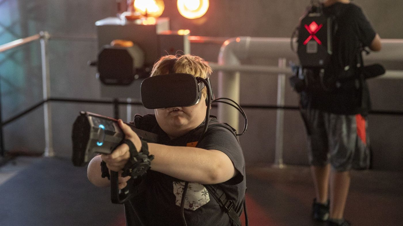 """Jack Dion, center, 10, and Kyle Mendoza, right, 14, of Santa Ana, play at the location-based virtual reality startup called """"Terminator Salvation: Fight for the Future"""" in the former Red Robin building at the Irvine Spectrum Center on Aug. 31, 2018. (Allen J. Schaben / Los Angeles Times)"""
