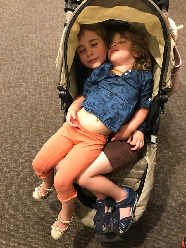 Traveling internationally and waiting in lines at the airport. Both kids, ages 3 and 6, rested in the stroller.