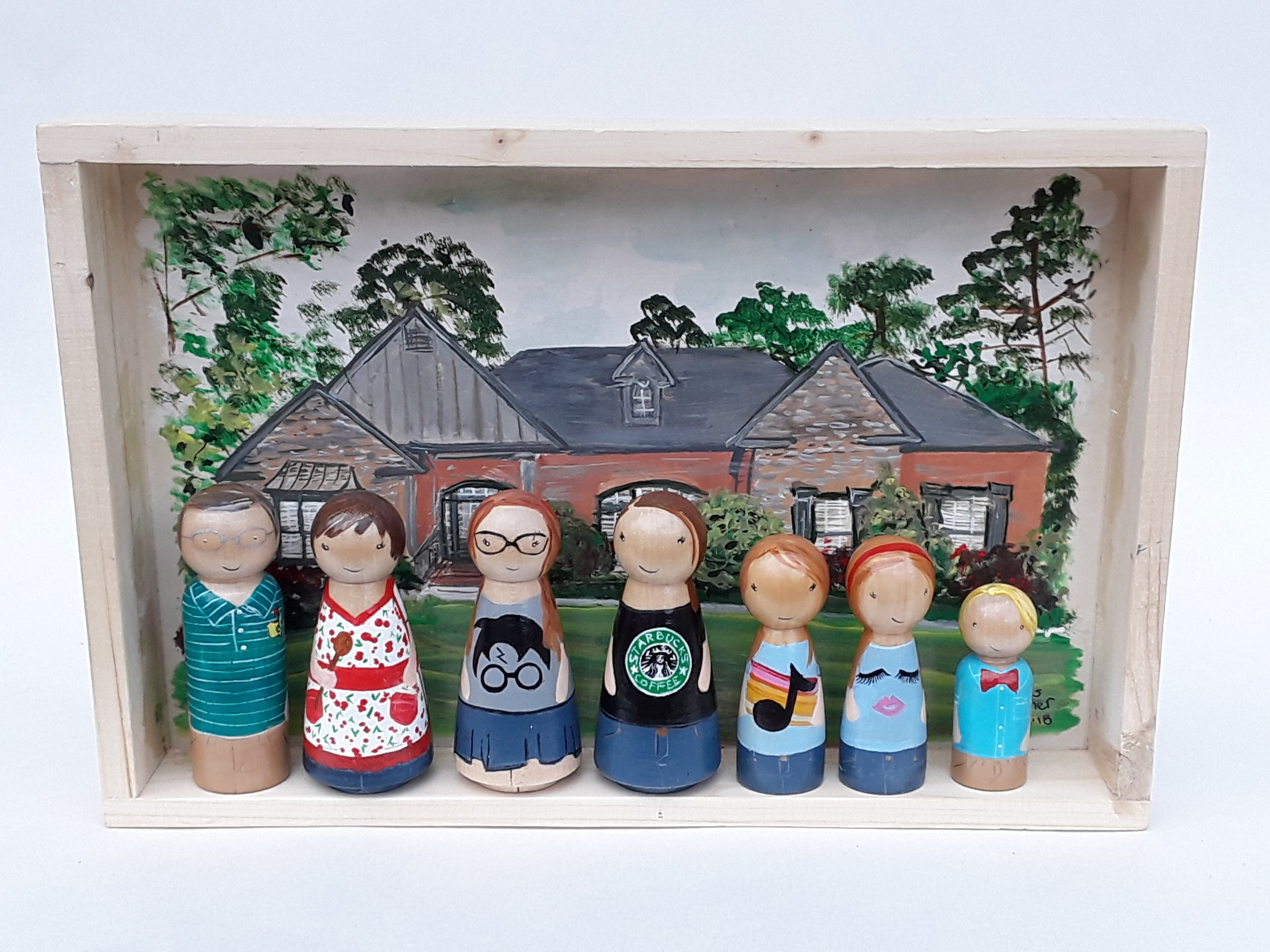 Grandparents and their grandchildren - This Shadow Box was created as a special gift for the Grandparents. A recreation of all their grandchildren standing in front of their treasured home. Each peg doll is wearing an outfit or details that are meaningful to them, from Grandpa's Golf shirt to grandma's wooden spoon.Box size 8x12 with 7 peg dolls.Starts at $180