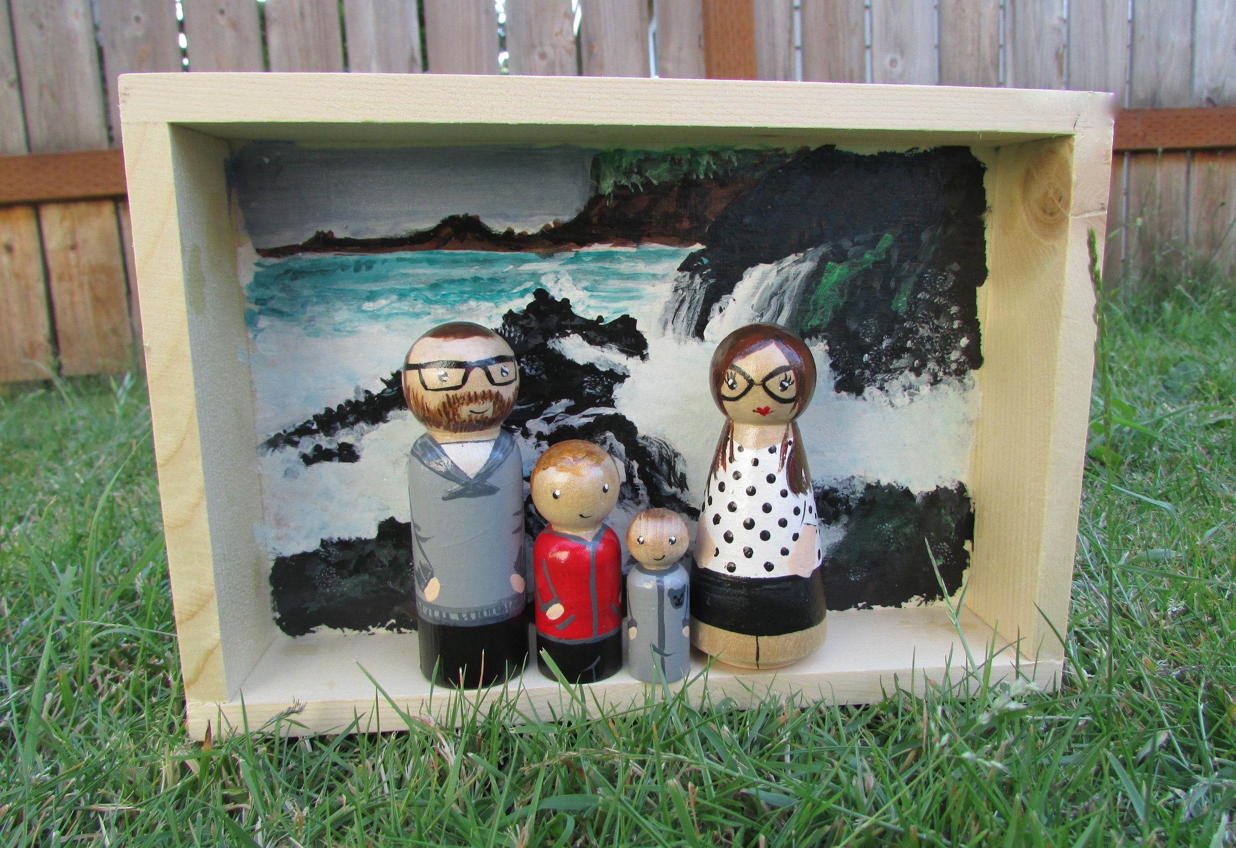 Remembering Home - This beautiful family were on the way to starting a new adventure in Germany when this Shadow Box was ordered. Back drop to their little family is their favorite beach in the Pacific North West and a way for them to remember their home while living up new adventures in their new home!Box size 6x8 inches. 4 peg dolls. Starts at $110